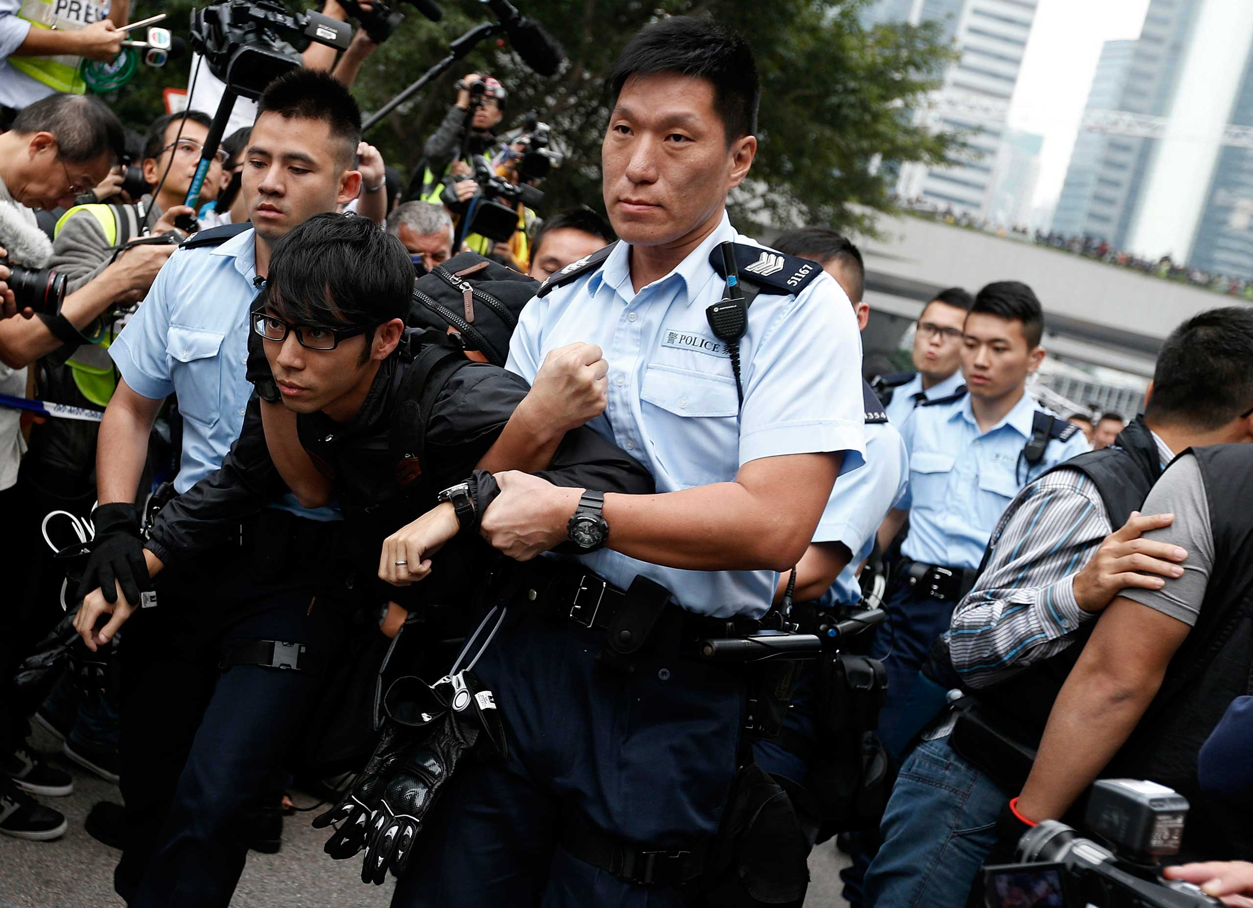 A demonstrator is taken away by policemen, at an area previously blocked by pro-democracy supporters, outside the government headquarters in Hong Kong, Dec. 11, 2014.