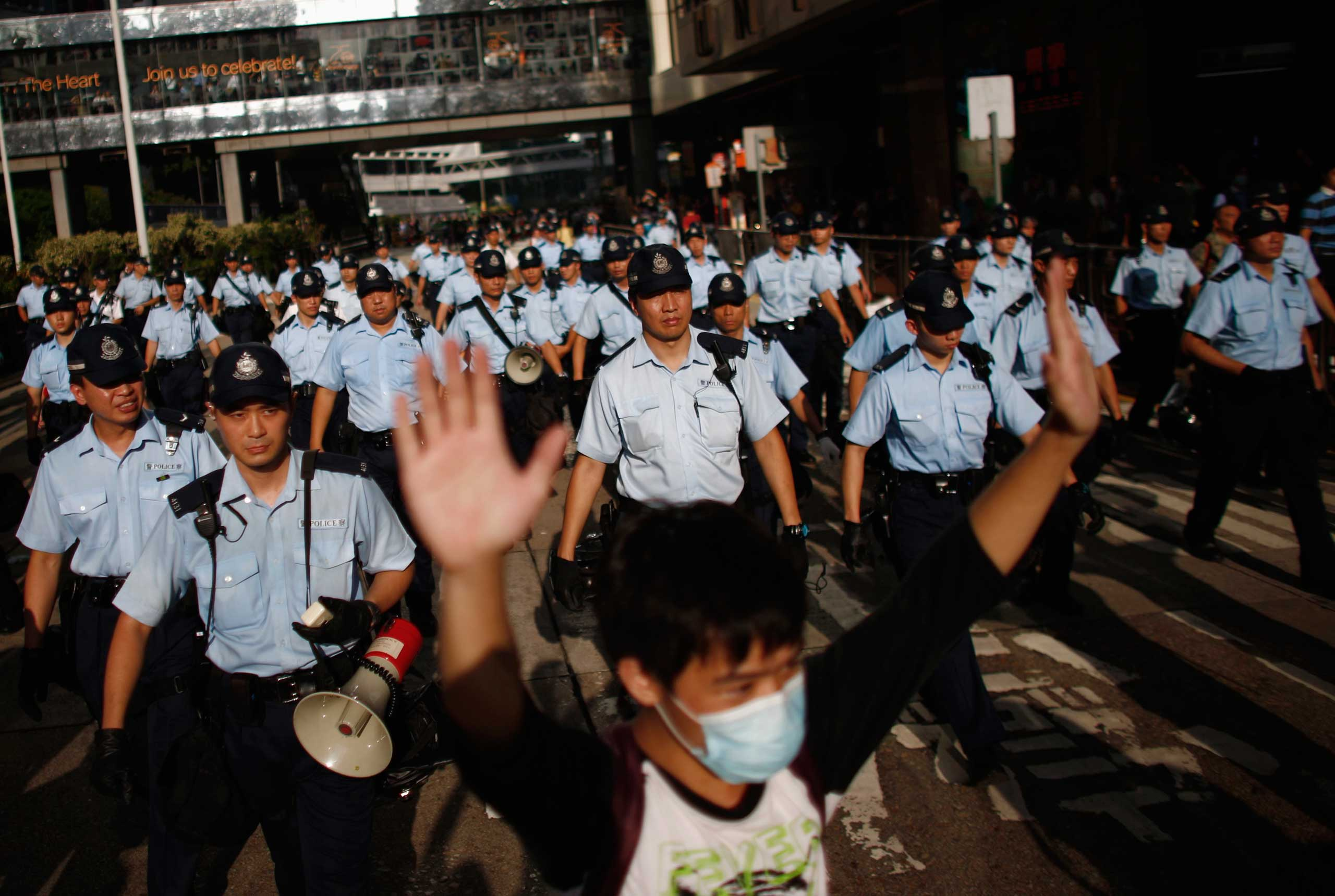A protester raises his arms as police officers try to disperse the crowd near the government headquarters in Hong Kong, Sept. 29, 2014.
