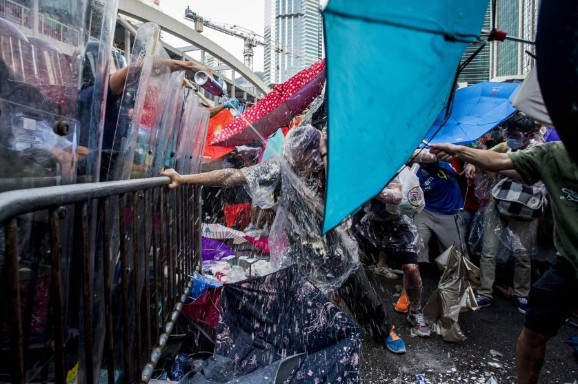 Pro-democracy demonstrators are sprayed with pepper spray during clashes with police officers during a rally near the Hong Kong government headquarters on Sept. 28, 2014.