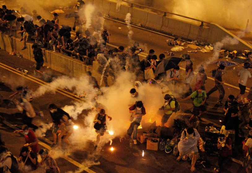 Riot police use tear gas against protesters after thousands of people blocked a main road at the financial central district in Hong Kong, Sept. 28, 2014.