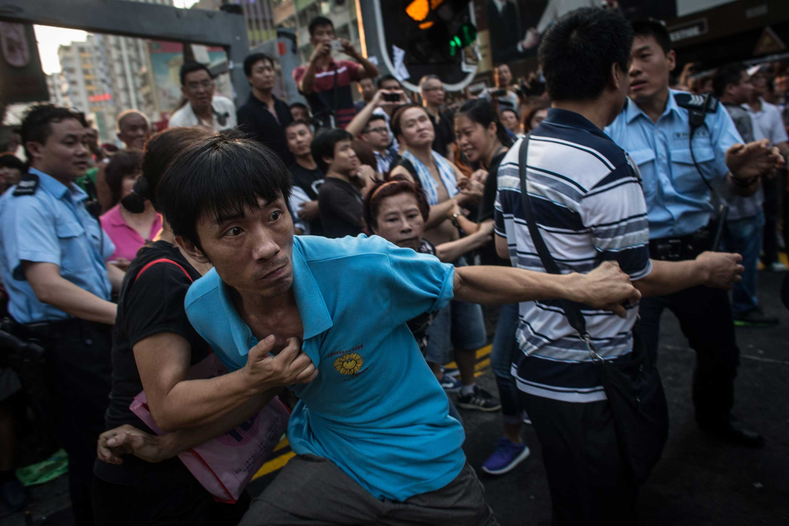 A local resident breaks through police lines and attempts to reach the pro-democracy tent on Oct. 3, 2014 in Mong Kok, Hong Kong.