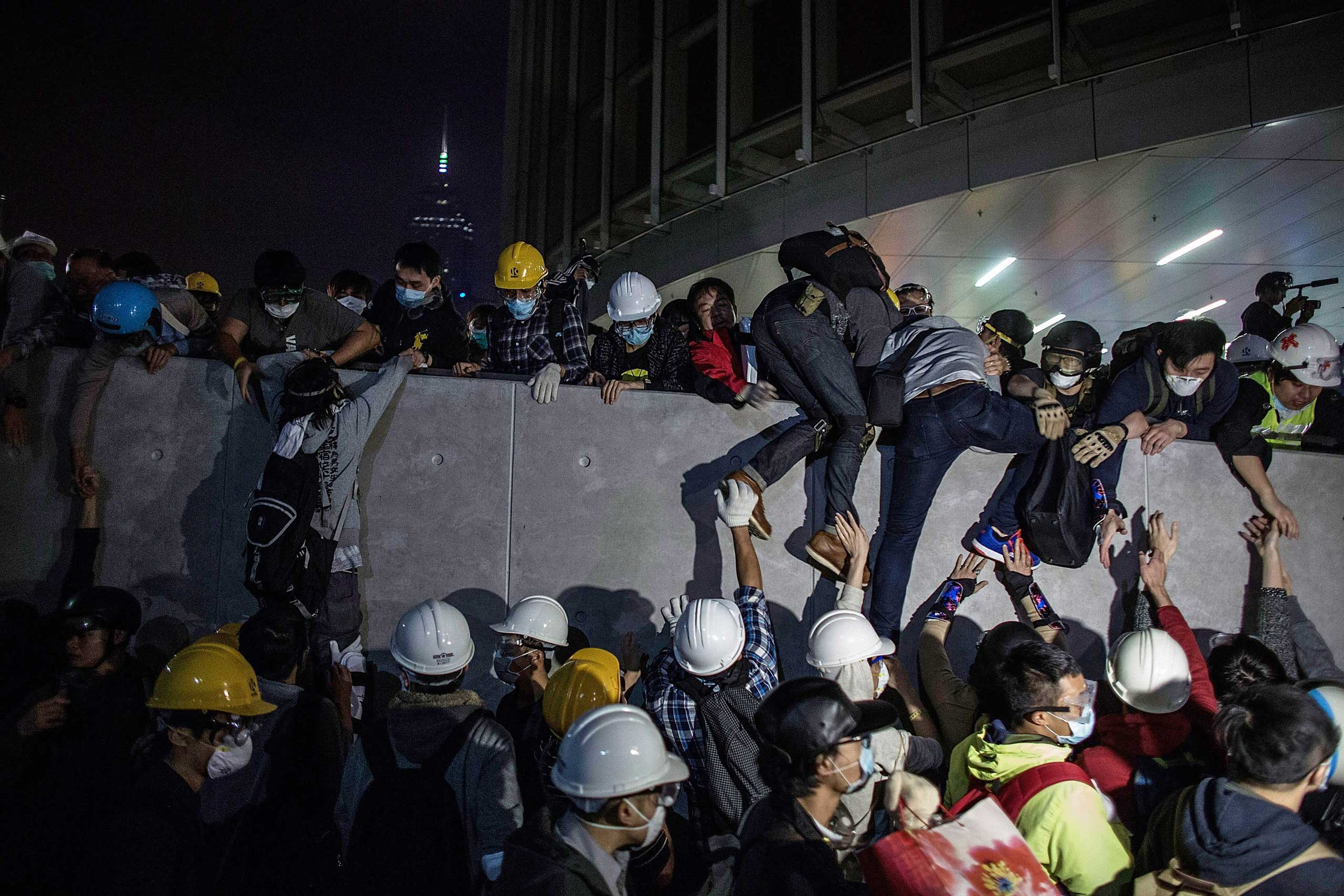 Pro-democracy protesters climb up a wall as police officers disperse them outside the Legislative Council building after clashes with pro-democracy activists on Nov. 19, 2014 in Hong Kong.