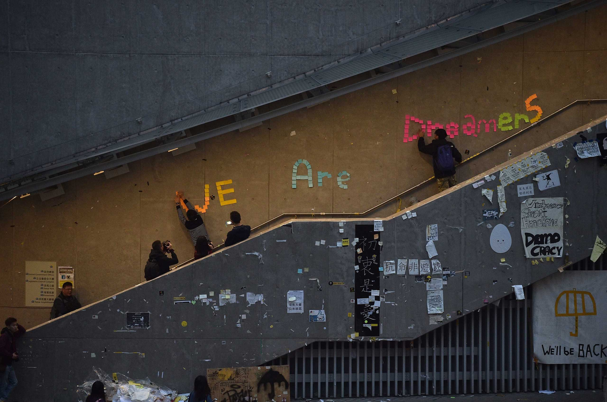 "Pro-democracy protesters remove signs placed up during the past two months of protests from the area around the protest camp but leave intact the notice ""We are dreamers"" in the Admiralty in Hong Kong on Dec. 11, 2014."