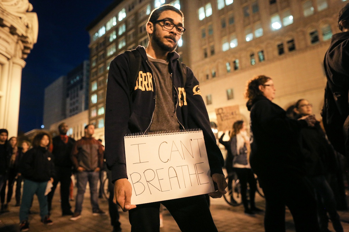 In Oakland, Calif., Niels Smith holds a sign reading  I can't breathe  on the second night of demonstrations following a Staten Island, New York grand jury's decision not to indict a police officer in the chokehold death of Eric Garner, on Dec. 4, 2014.