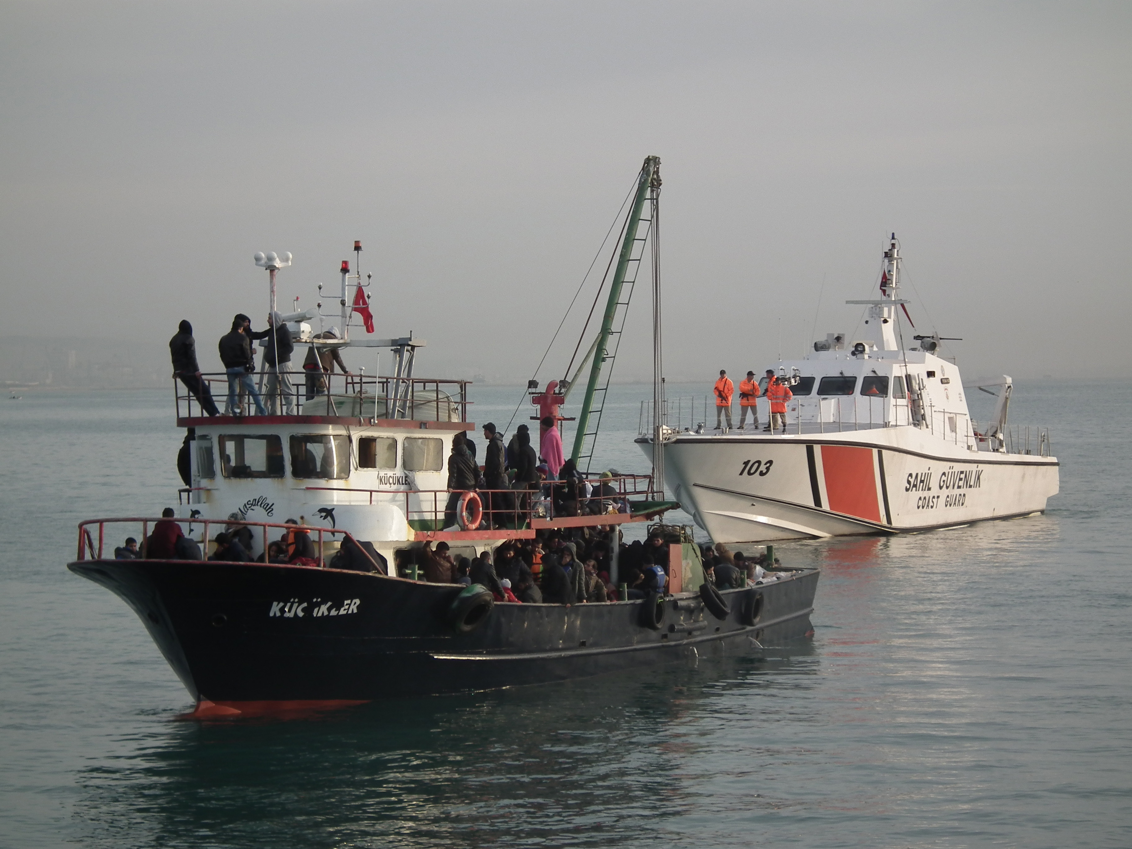 Illegal immigrants are escorted by the officers of Turkey's Coast Guard Mediterranean Region Command as they arrive in Mersin, Turkey on Dec. 6, 2014.