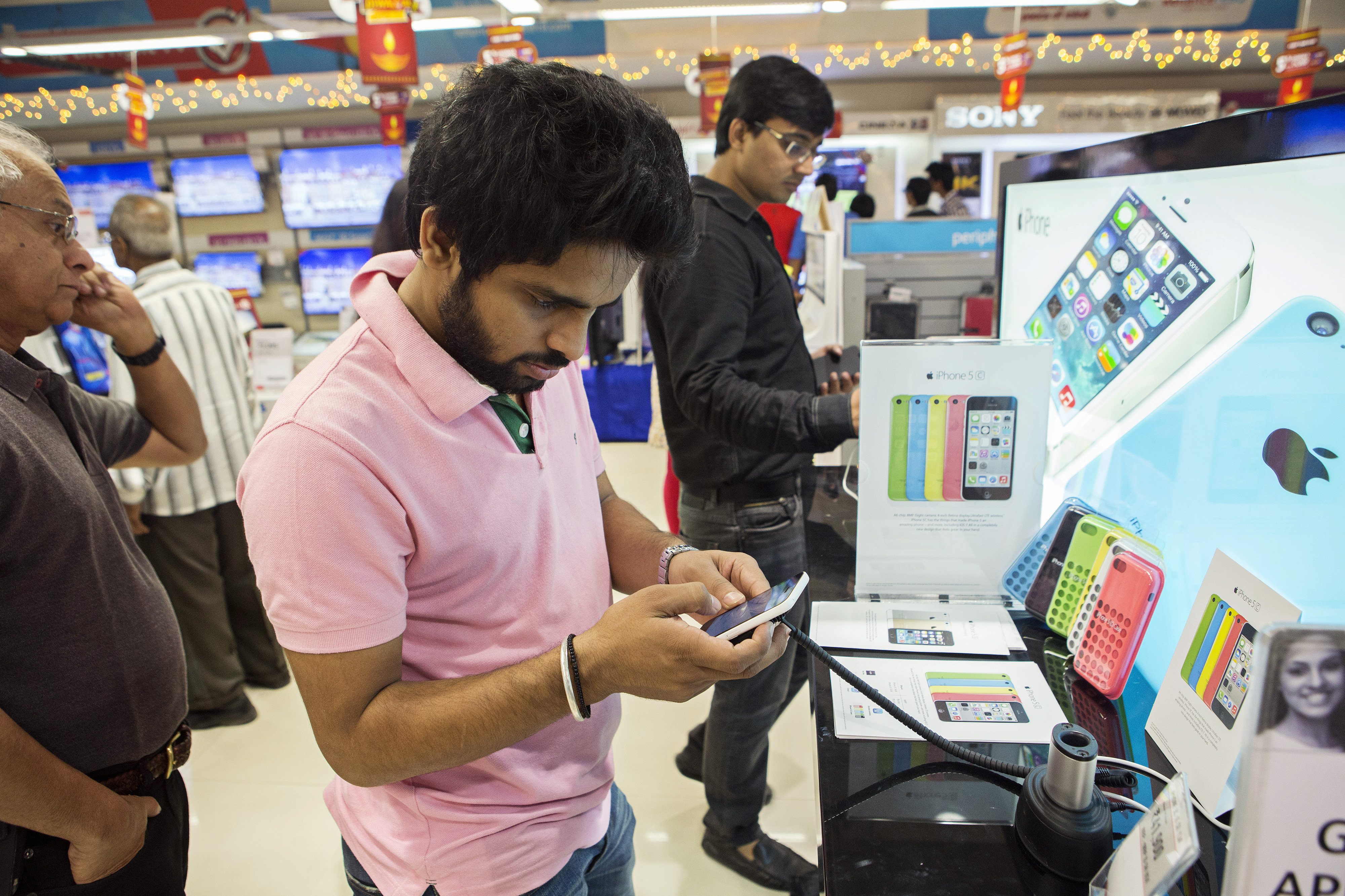 A customer tries out an Apple Inc. iPhone 5C at a Reliance Digital store, a subsidiary of Reliance Industries Ltd., in New Delhi, India, on Saturday, Nov. 2, 2013.