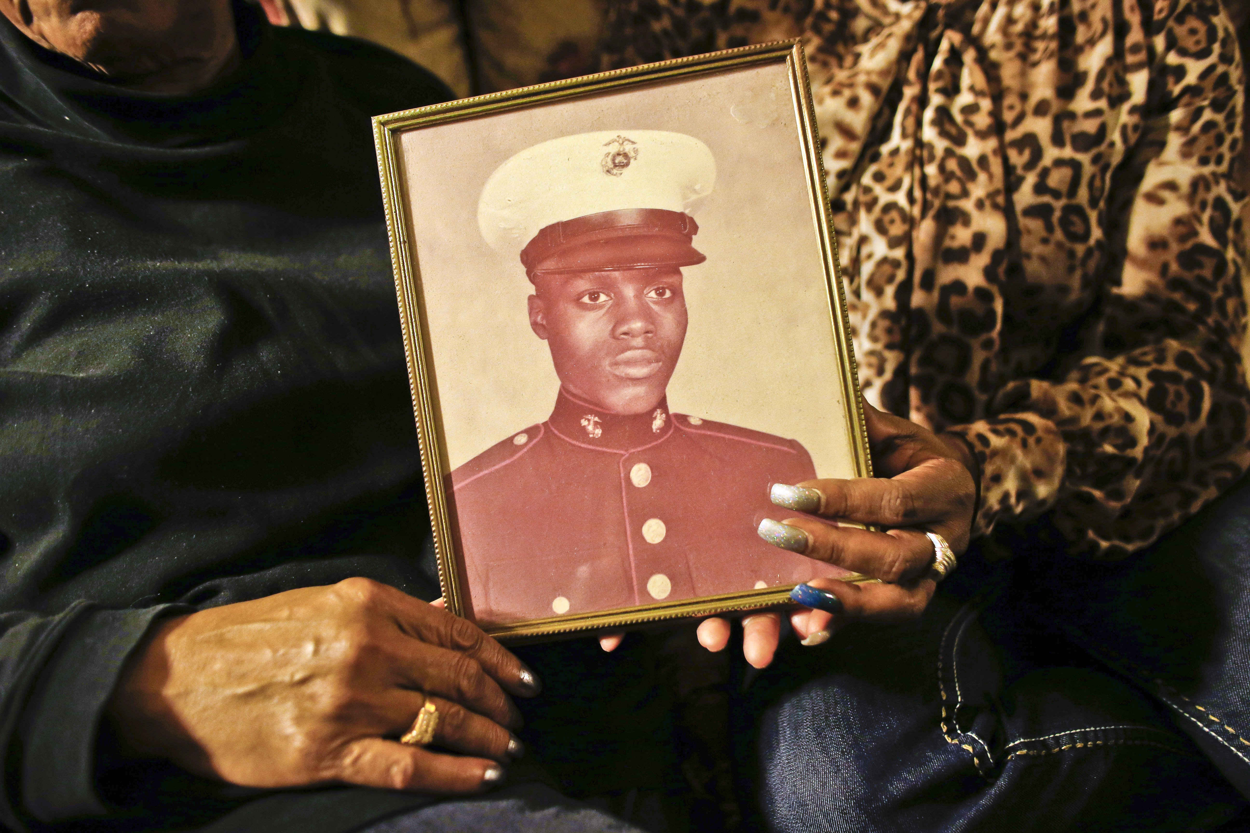 A picture of Jerome Murdough, a former homeless Marine who died in a mental observation unit on Rikers Island jail on Feb. 15, 2014 is held by his mother Alma Murdough left, and sister Cheryl Warner at Alma Murdough's home in the Queens borough of New York.
