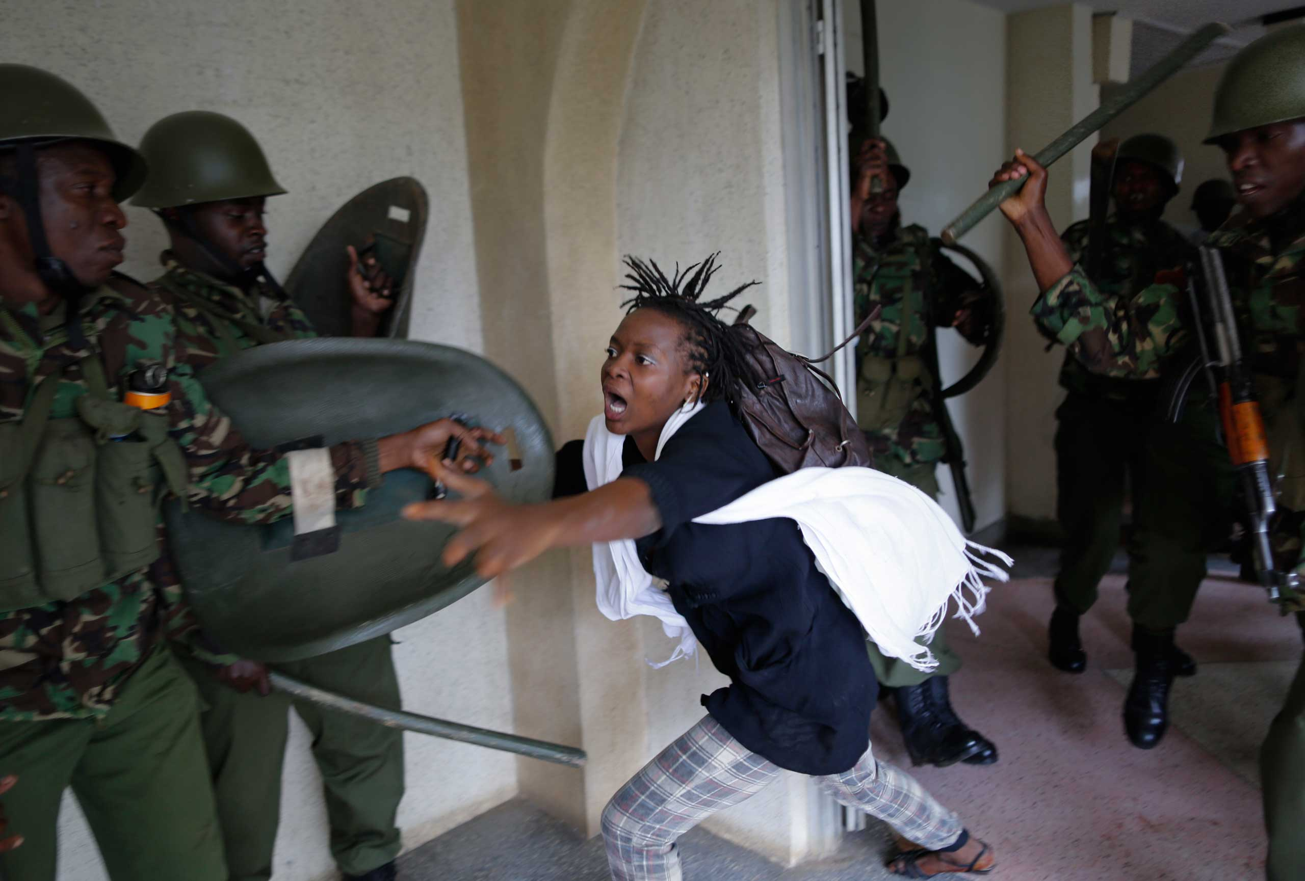 Kenya: Protests against tuition fee hikesA woman flees as a riot police officer beats her with a baton, after chasing protesting students into the Nairobi University campus in Nairobi, Kenya, May 20, 2014.