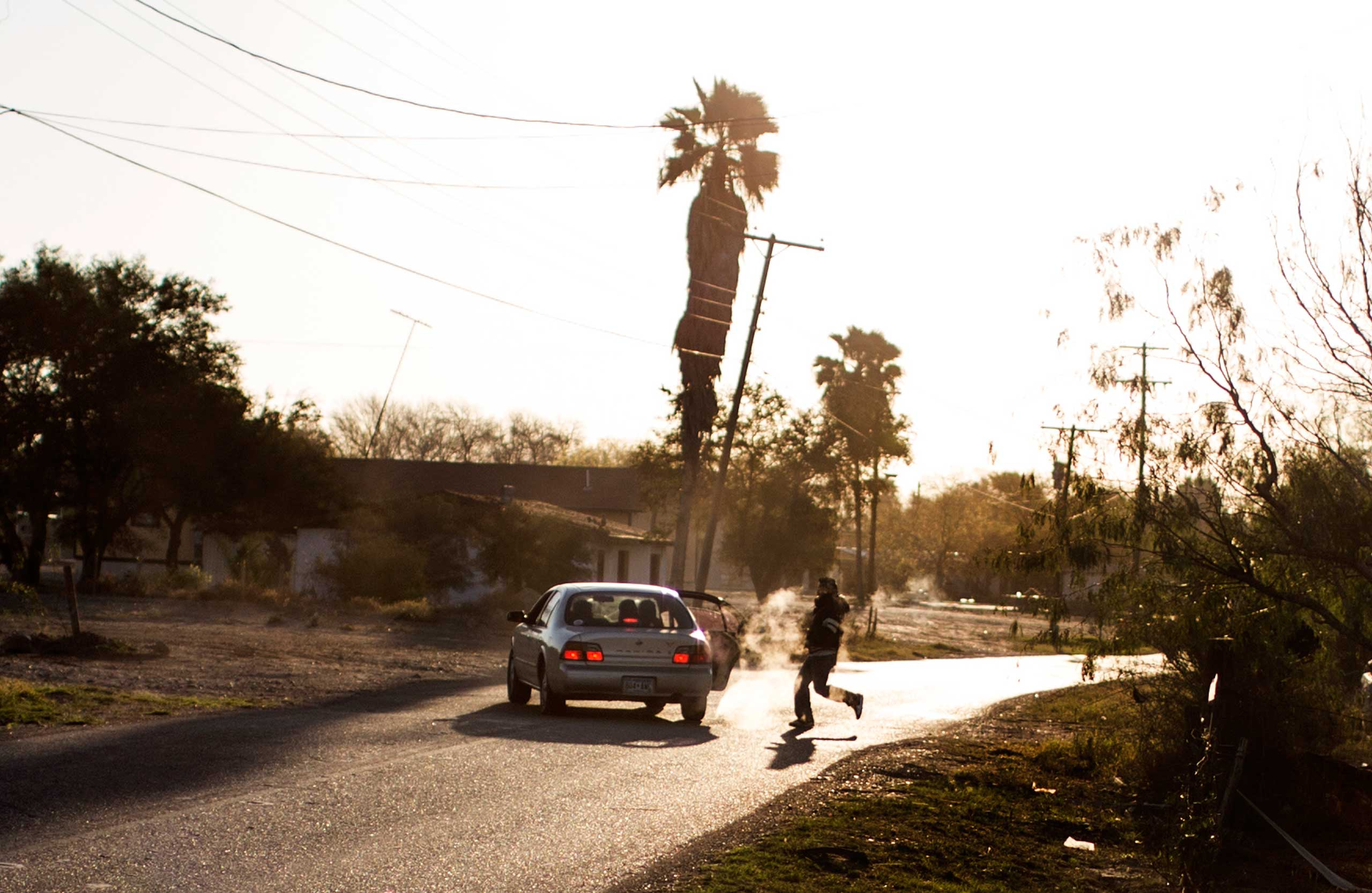 Migrants run from a gap in the border fence to a waiting car in the early morning in Penitas, Texas, Feb. 14, 2013.