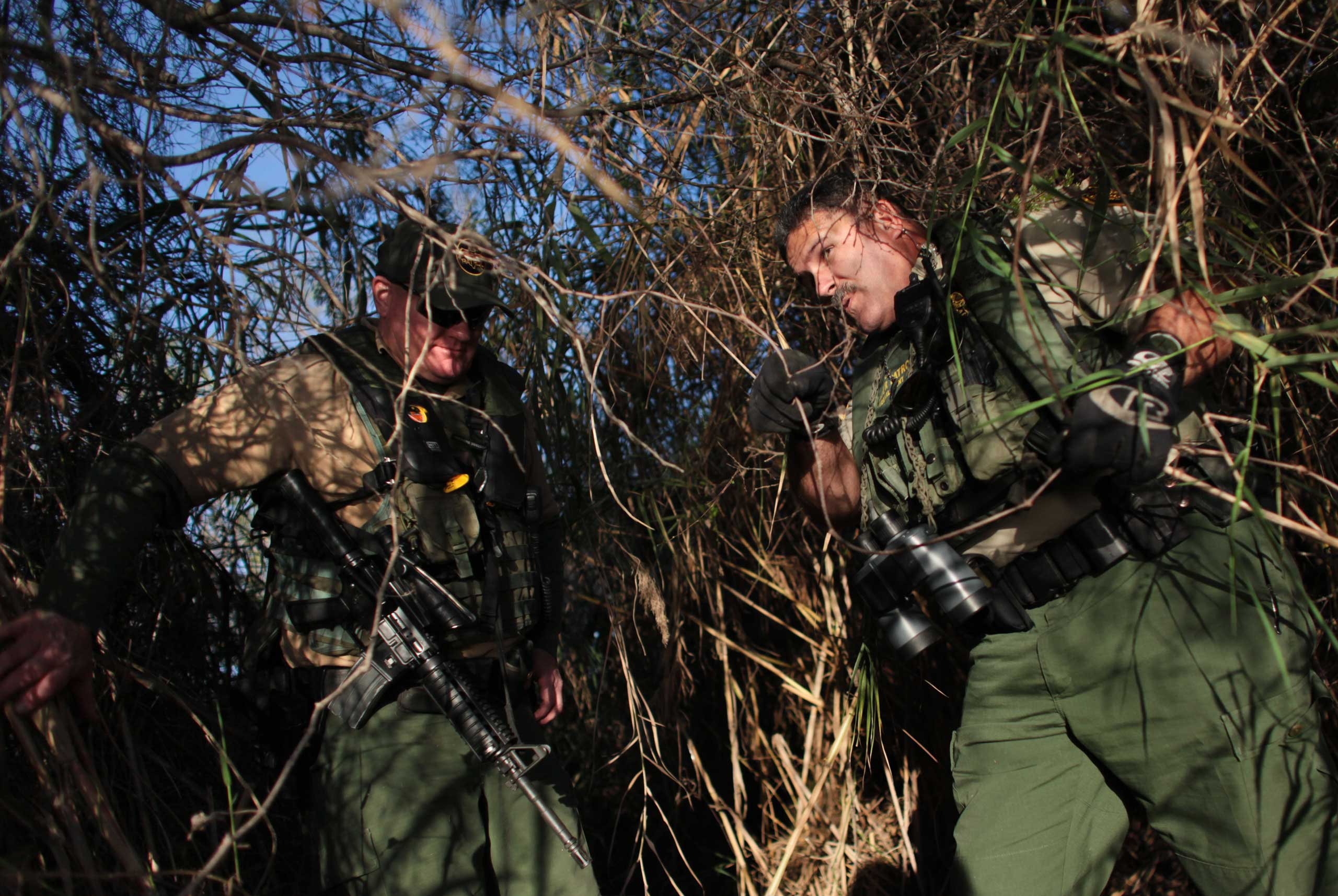 Border Patrol agents patrol the thick brush along the banks of the Rio Grande south of Mission, Texas on Feb. 13, 2013.