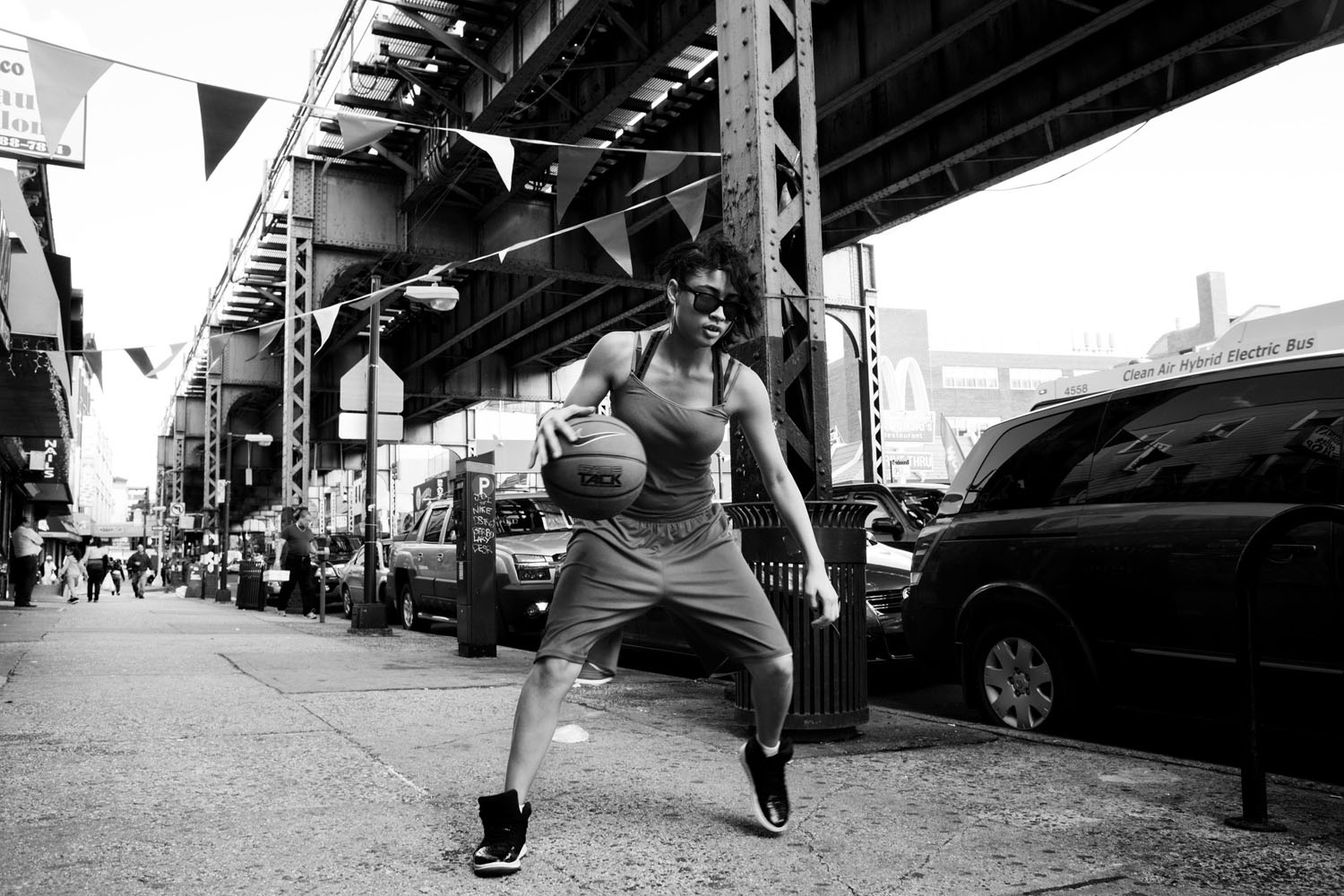 The New York Times: Perfect Timing on the Right Side of the TracksA young woman playing basketball on Broadway near Whipple Street, next to the JMZ subway line, Brooklyn.