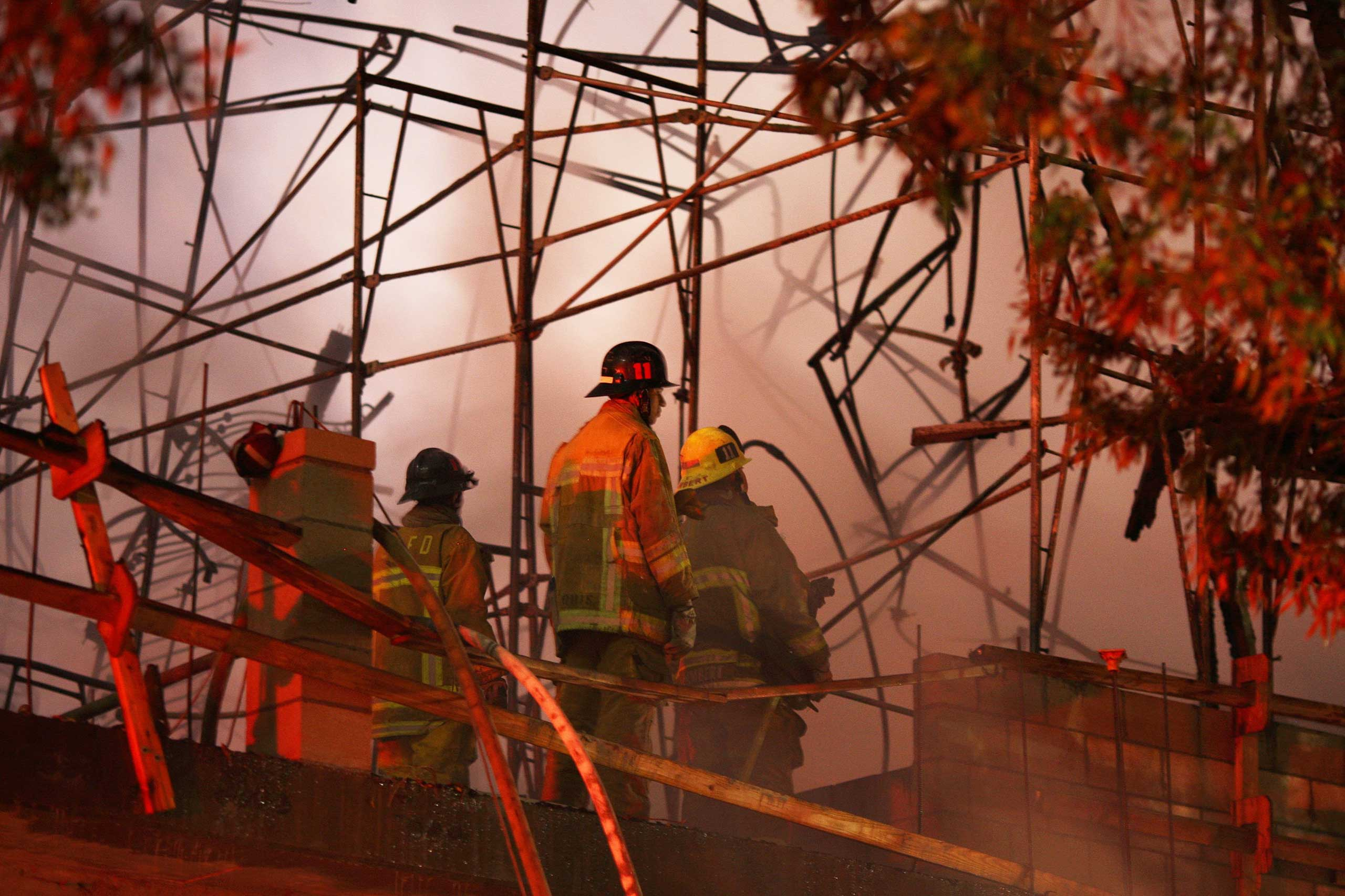 Los Angeles County firefighters battle a blaze at an apartment building under construction next to the Harbor CA-110 Freeway in Los Angeles on Dec. 8, 2014.