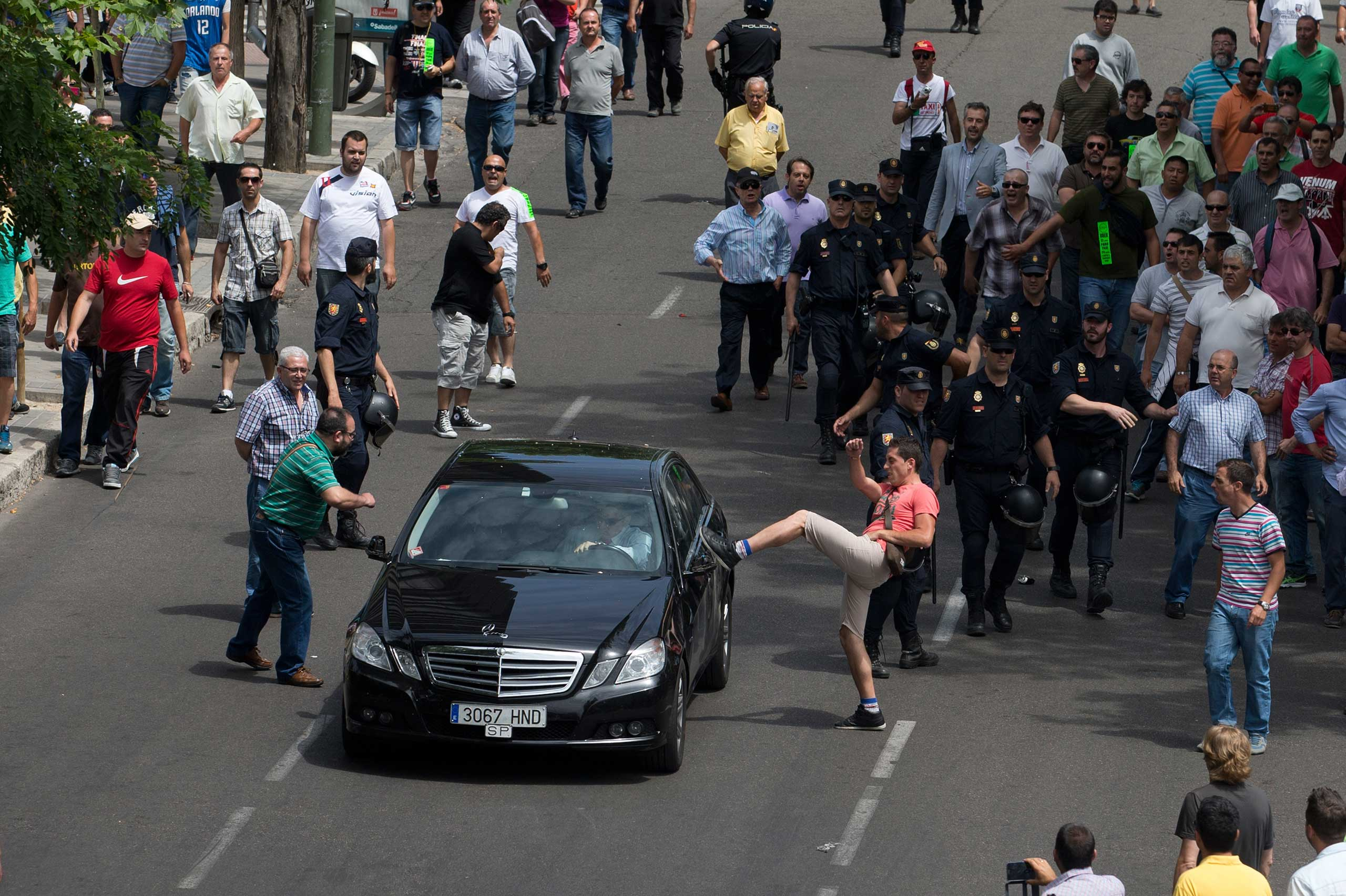 A demonstrator kicks a car, suspected of being a private taxi during a 24 hour taxi strike and protest in Madrid on June 11, 2014.