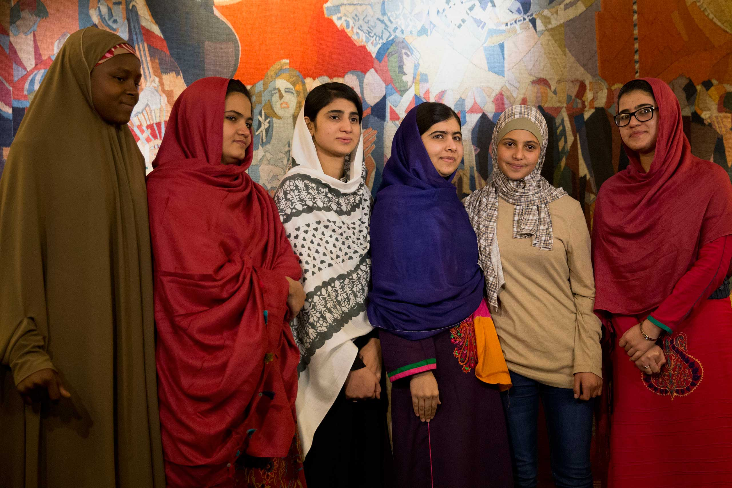 Joint Nobel Peace prize winner Malala Yousafzai, stands with five young women she invited to attend the Nobel Peace Prize ceremony, from left, Nigeria's Amina Yusuf, Pakistan's Kainat Soomro, school friend Shazia Ramzan, Syria's Mezon Almellehan and school friend Kainat Riaz, as they pose for a group photograph before speaking to the media at Malala's hotel in Oslo, Norway, Dec. 9, 2014.