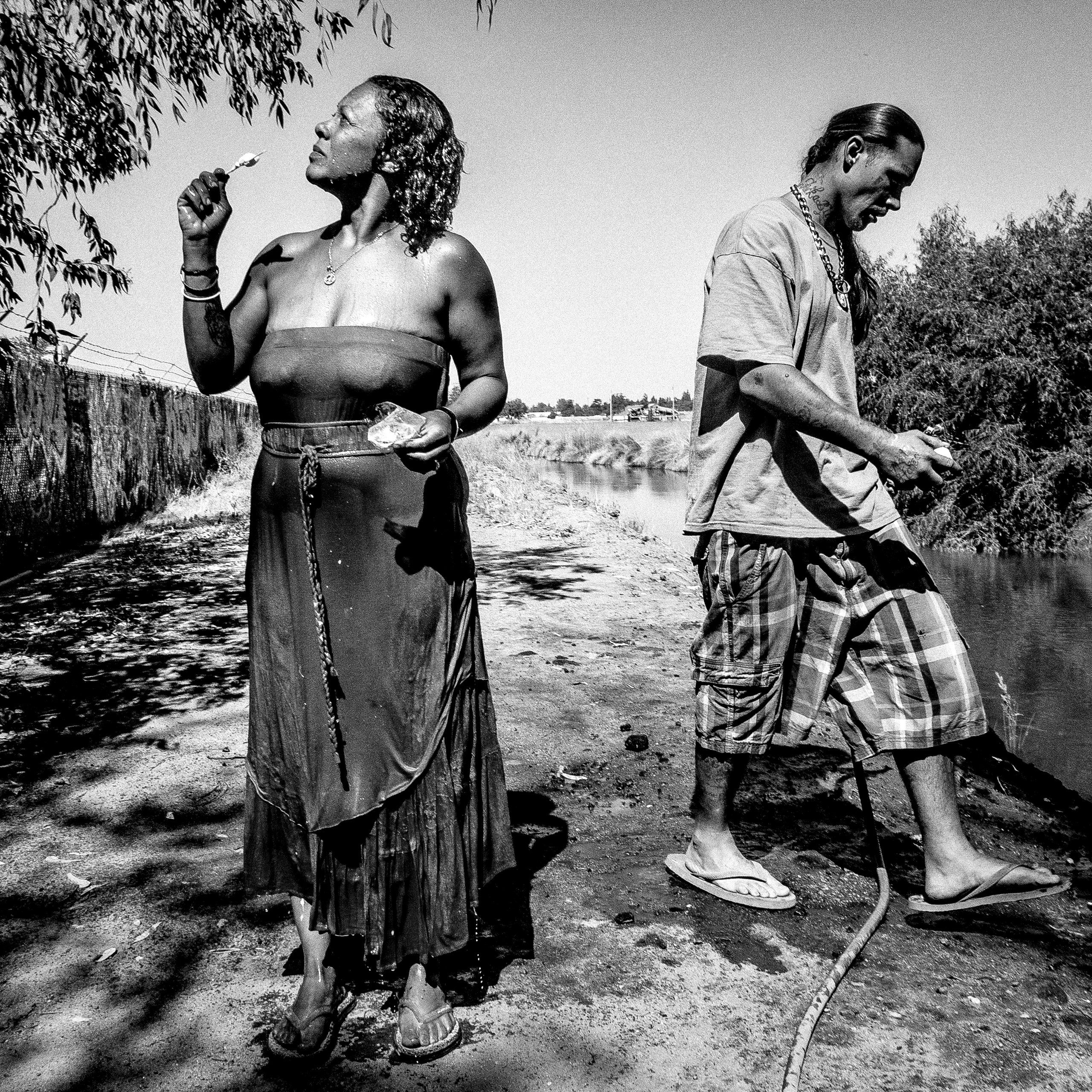 Ditchbank.  Fresno, CA.  Sinamon and Aaron bathe at an irrigation canal near their homeless encampment on the outskirts of Fresno.