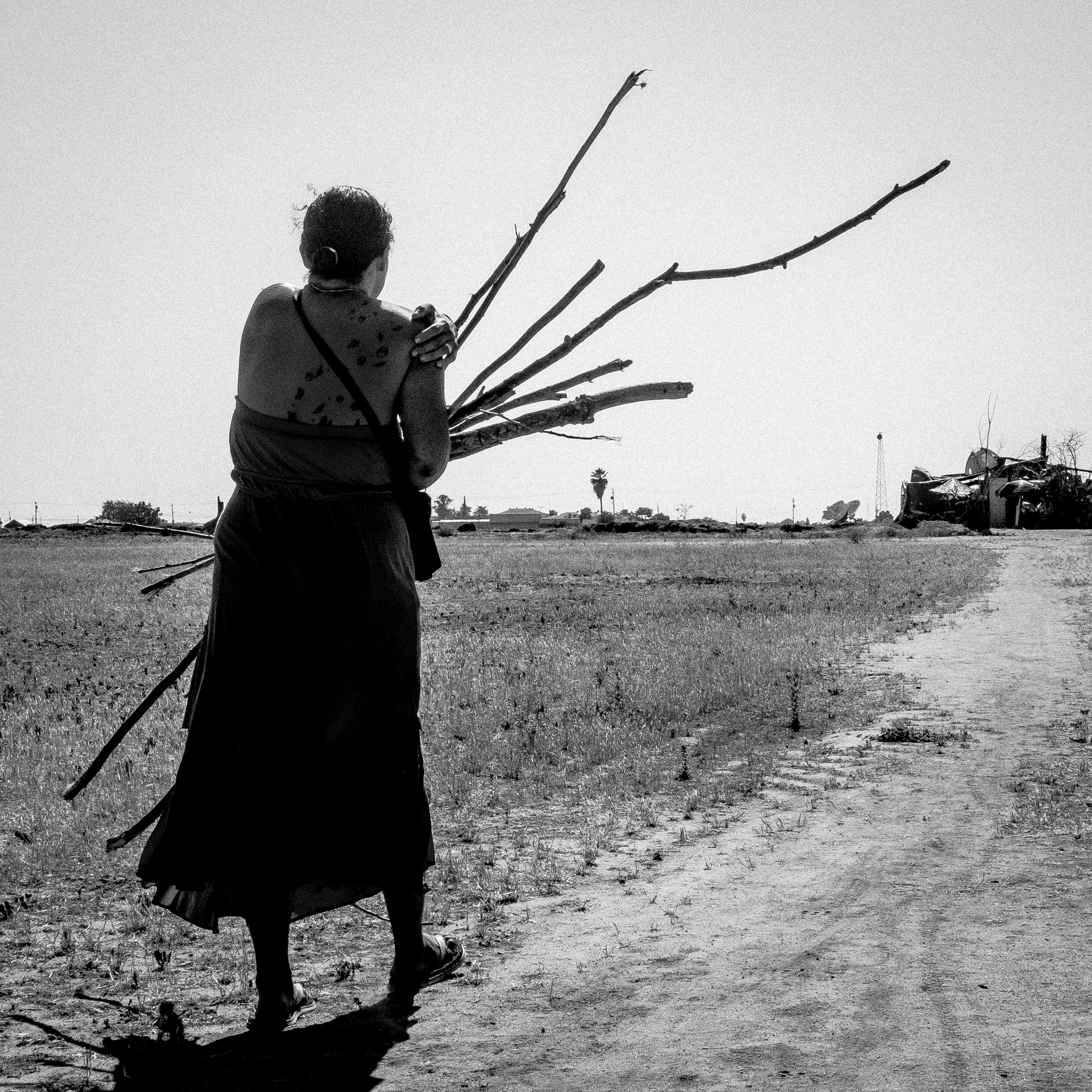 Sinamon carries firewood to the makeshift home she built in an empty lot just outside of Fresno.