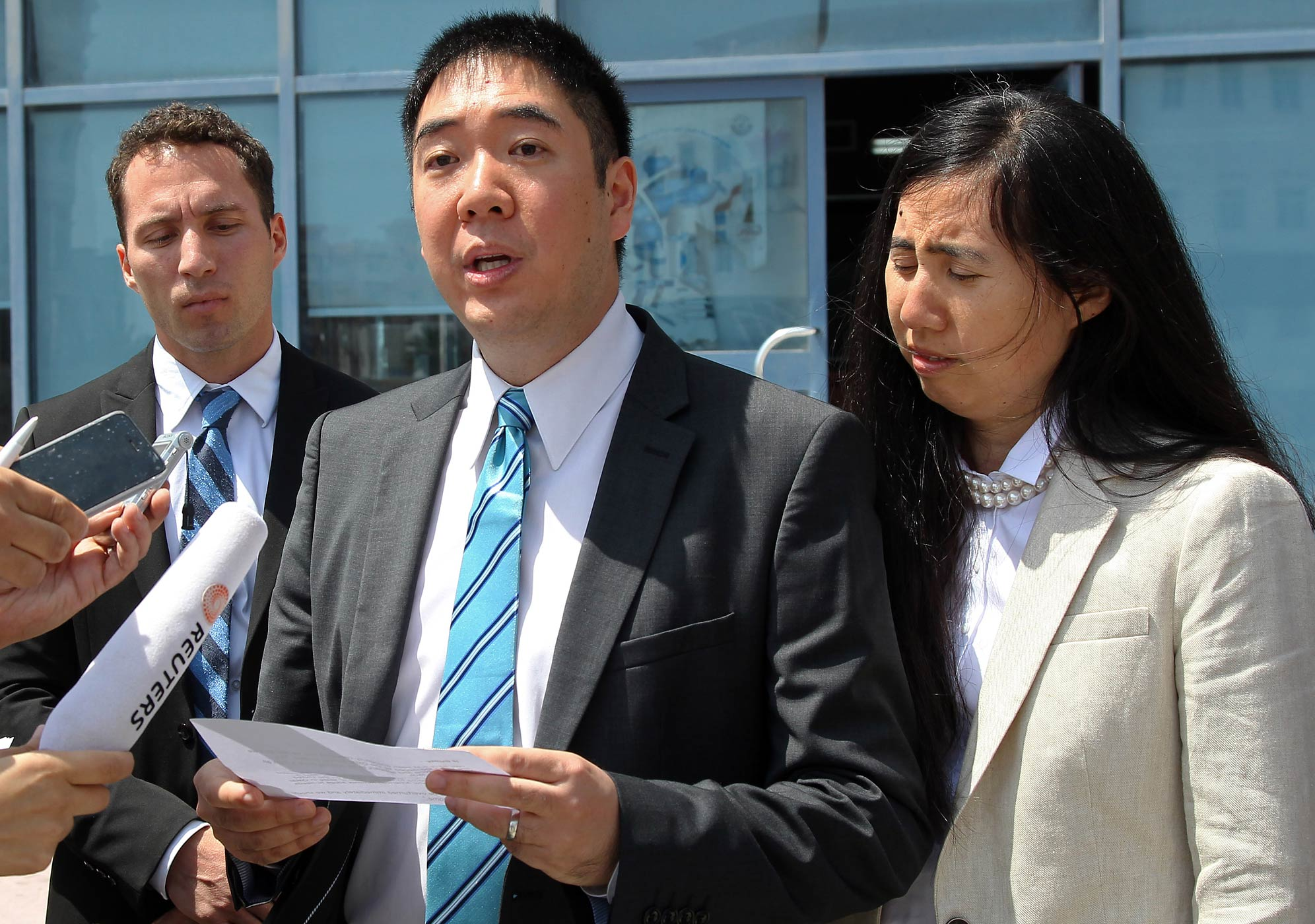 Matthew, left, and Grace Huang, an American couple charged with starving to death their 8-year-old adopted daughter, speak to the press outside the a courthouse before their trial in Doha, Qatar, Thursday, March 27, 2014.
