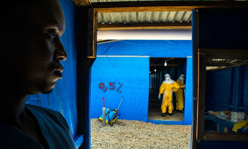 Moses Tarkulah stands by as colleagues enter the suspected Eloba case ward Bong County Ebola Treatment Unit, Sept. 16, 2014.