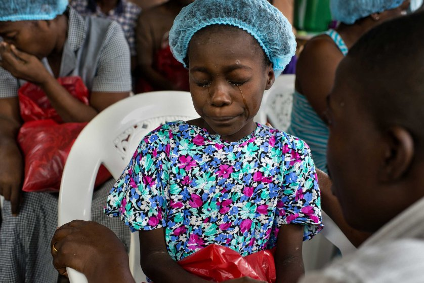 Esther Tokpah, 11 an orphan, weeps as Dr. Jerry Brown tries to console her before she was released from care on Sept. 24, 2014 in Monrovia, Liberia.