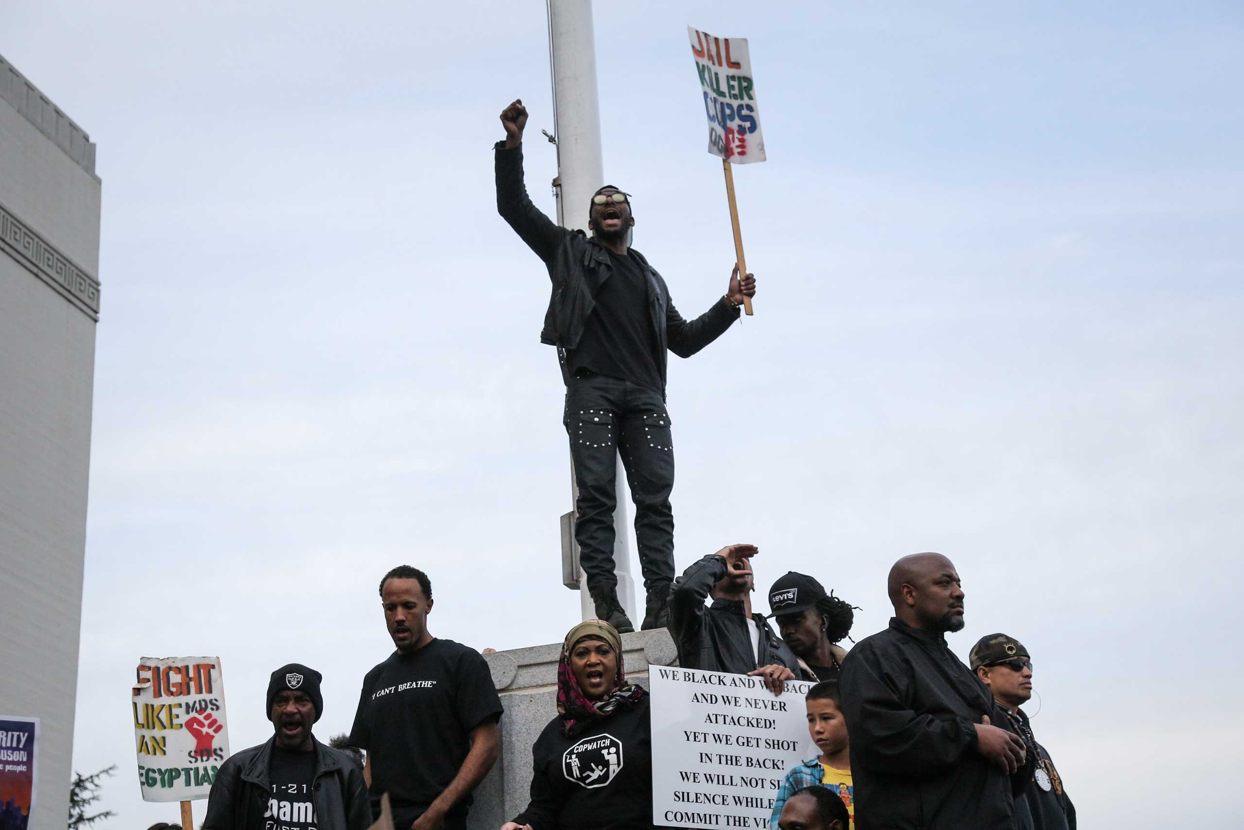 A man holds up a ''Jail Killer Cops' sign during a 'Millions March' demonstration in Oakland, Calif. on Dec. 13, 2014.