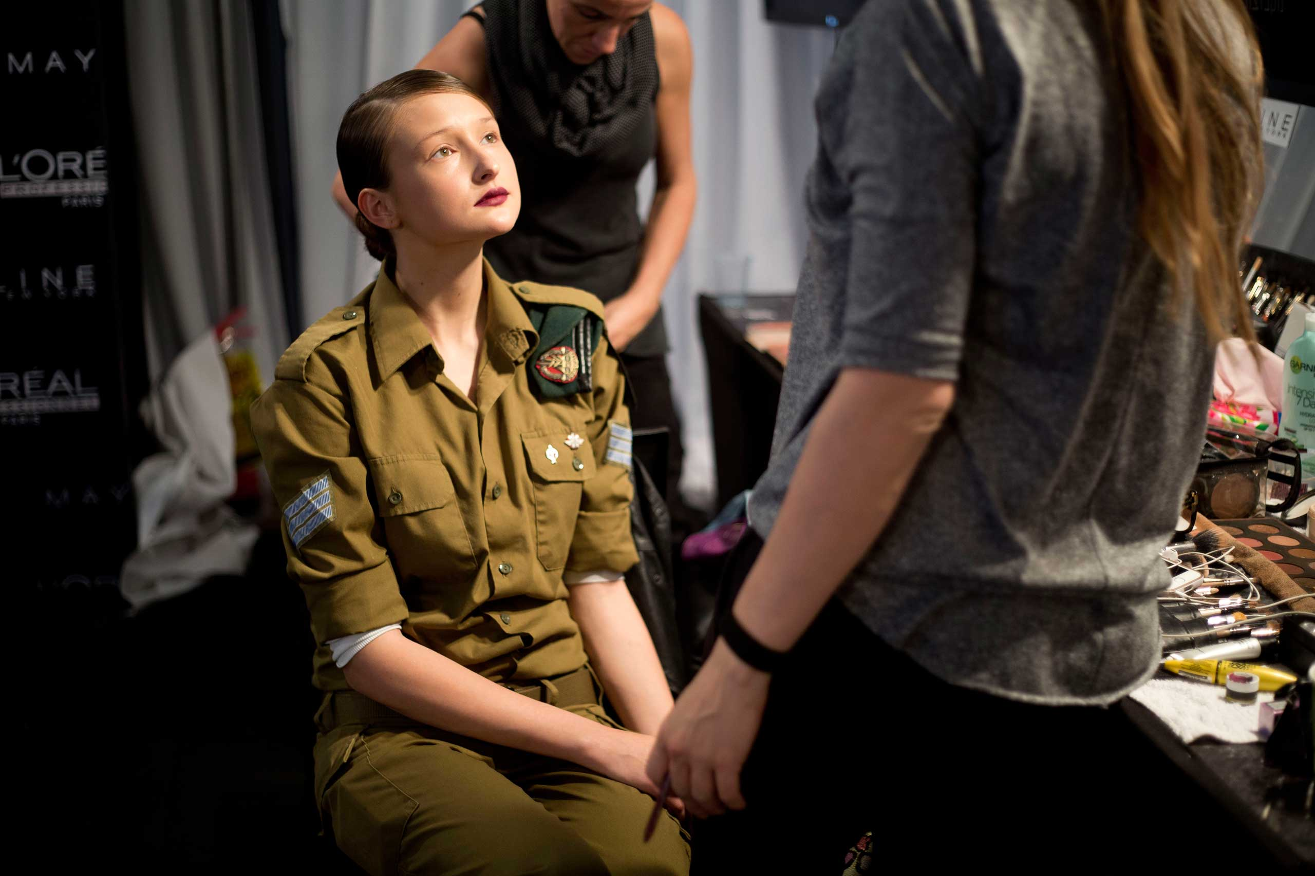 An Israeli model, who serves in the military, wears her uniform in the makeup chair before her turn on the catwalk of a show by Israeli designer Dorin Frankfurt at the Tel Aviv fashion week in Israel, March 11, 2014.