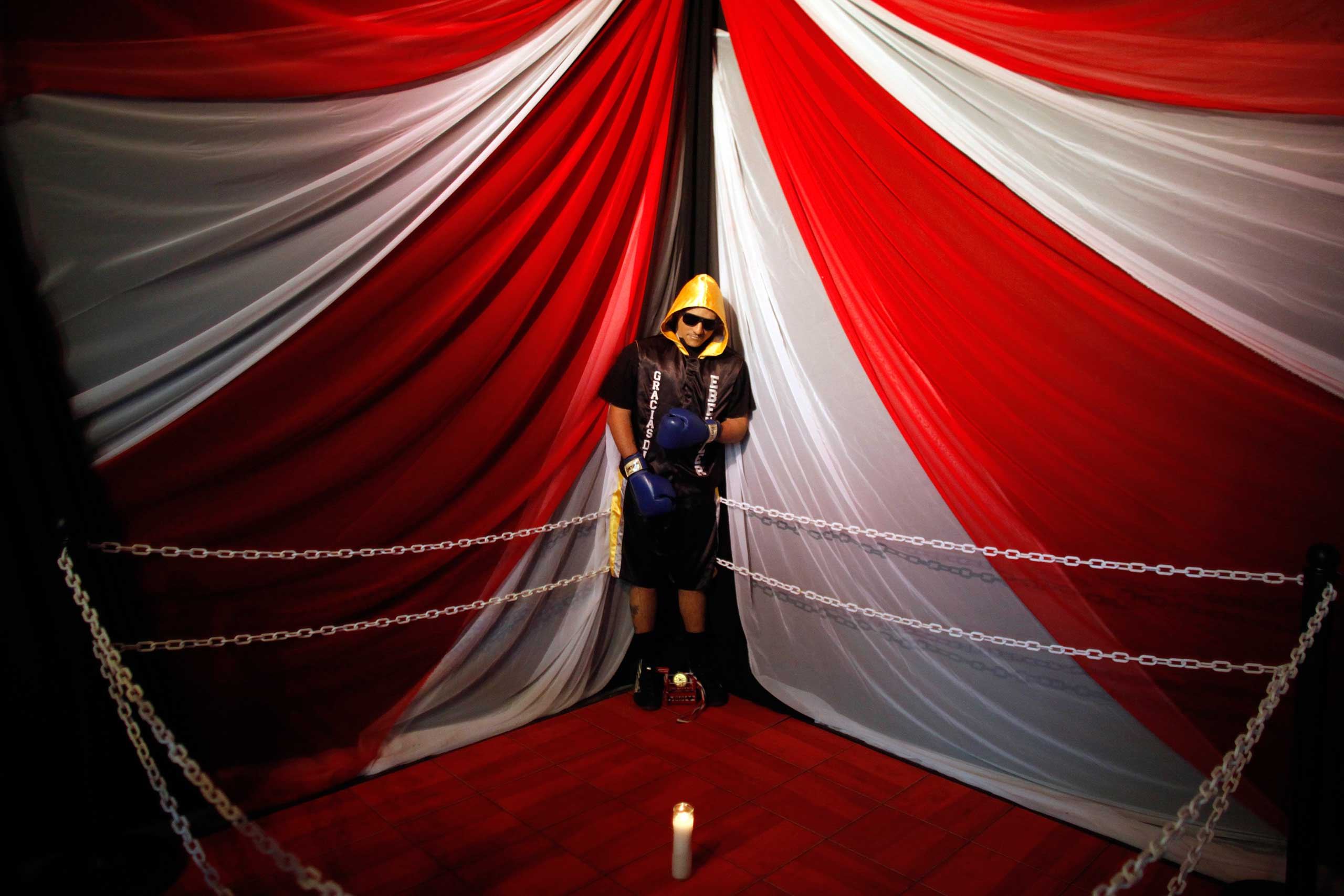 The body of boxer Christopher Rivera, who was shot to death, is propped up in a fake boxing ring during his wake at the community recreation center within the public housing project where he lived in San Juan, Puerto Rico, Jan. 31, 2014.