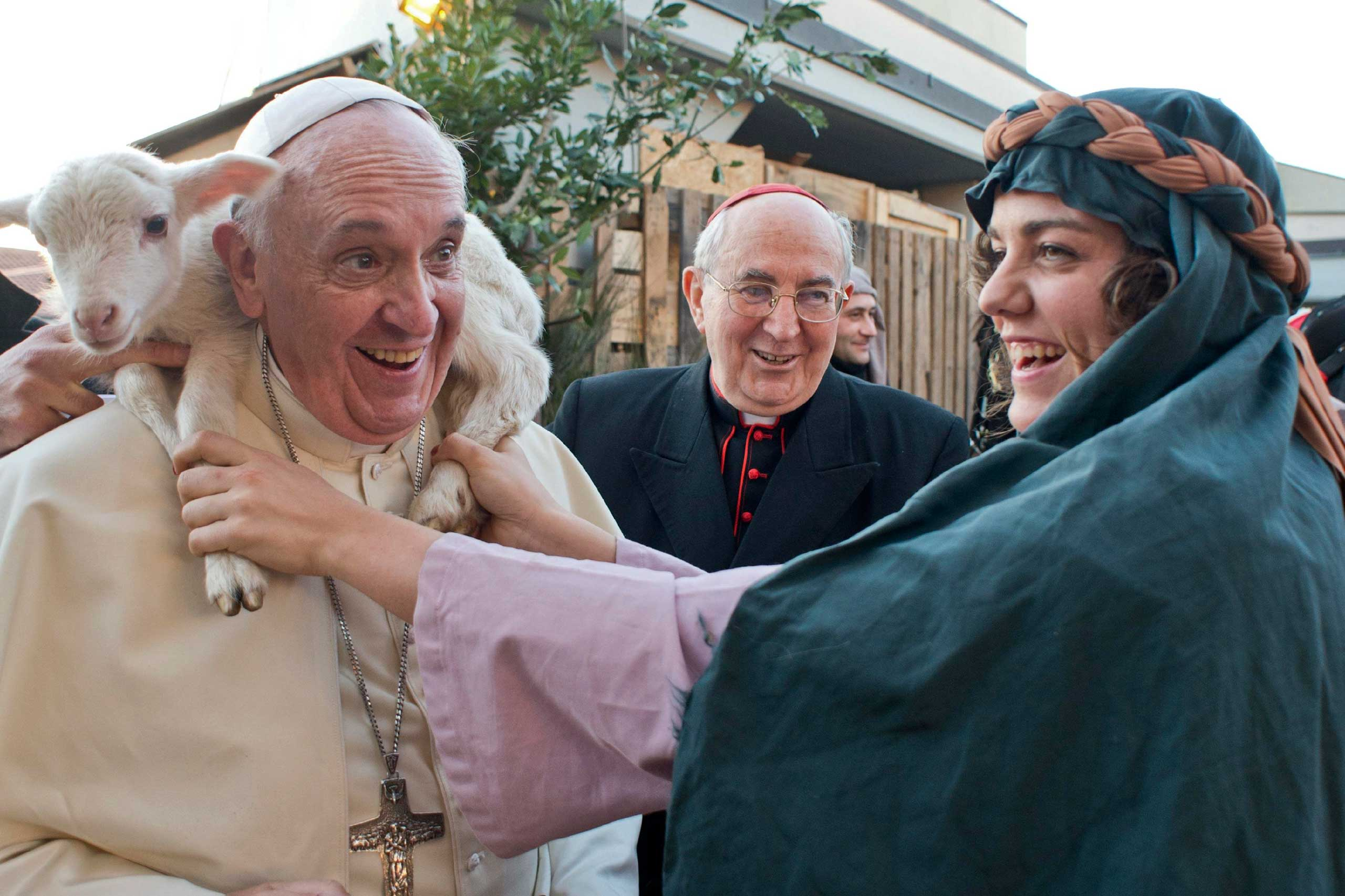 A woman dressed as a character from the nativity scene puts a lamb around the neck of Pope Francis as he arrives to visit the Church of St. Alphonsus Maria de Liguori in the outskirts of Rome, Jan. 6, 2014.