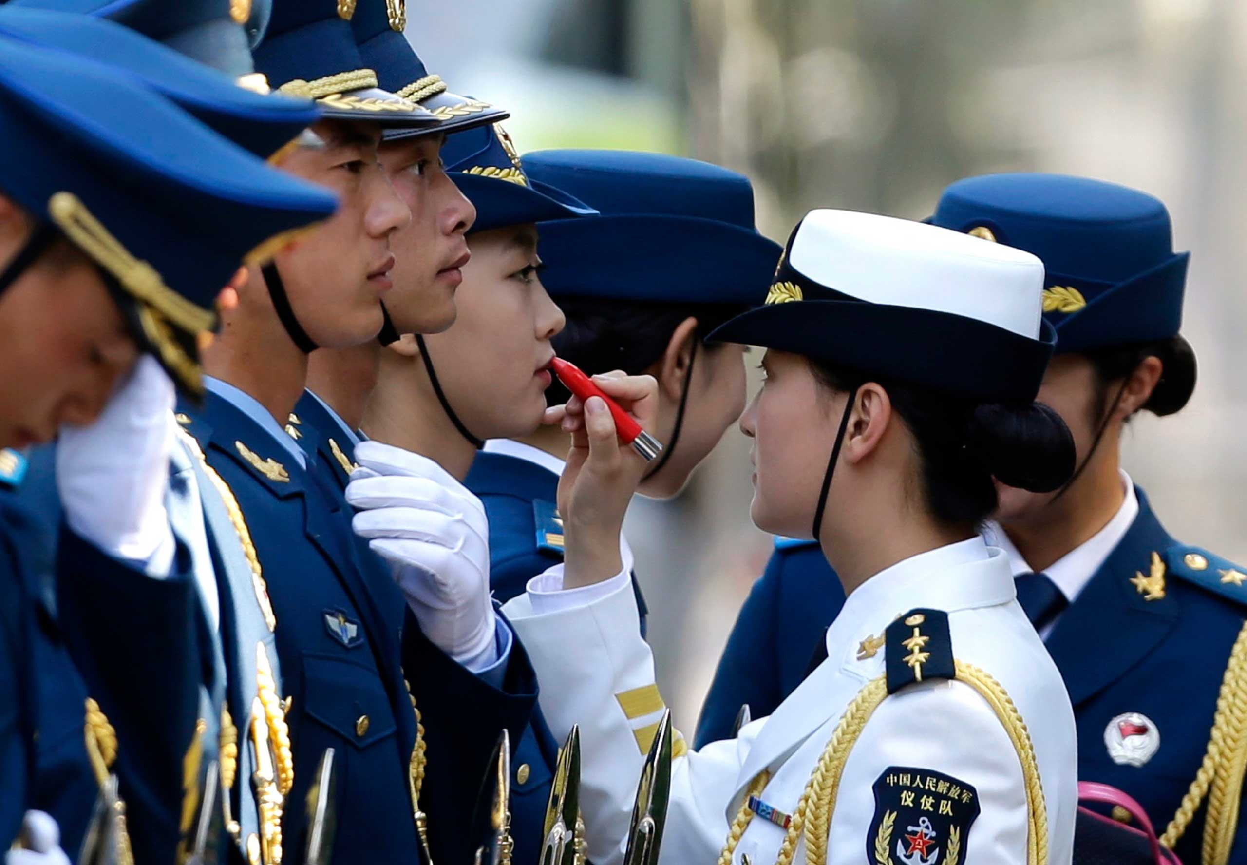 A female honor guard has lipstick applied as they prepare for an official welcoming ceremony for Italy's Prime Minister Matteo Renzi outside the Great Hall of the People in Beijing, June 11, 2014.