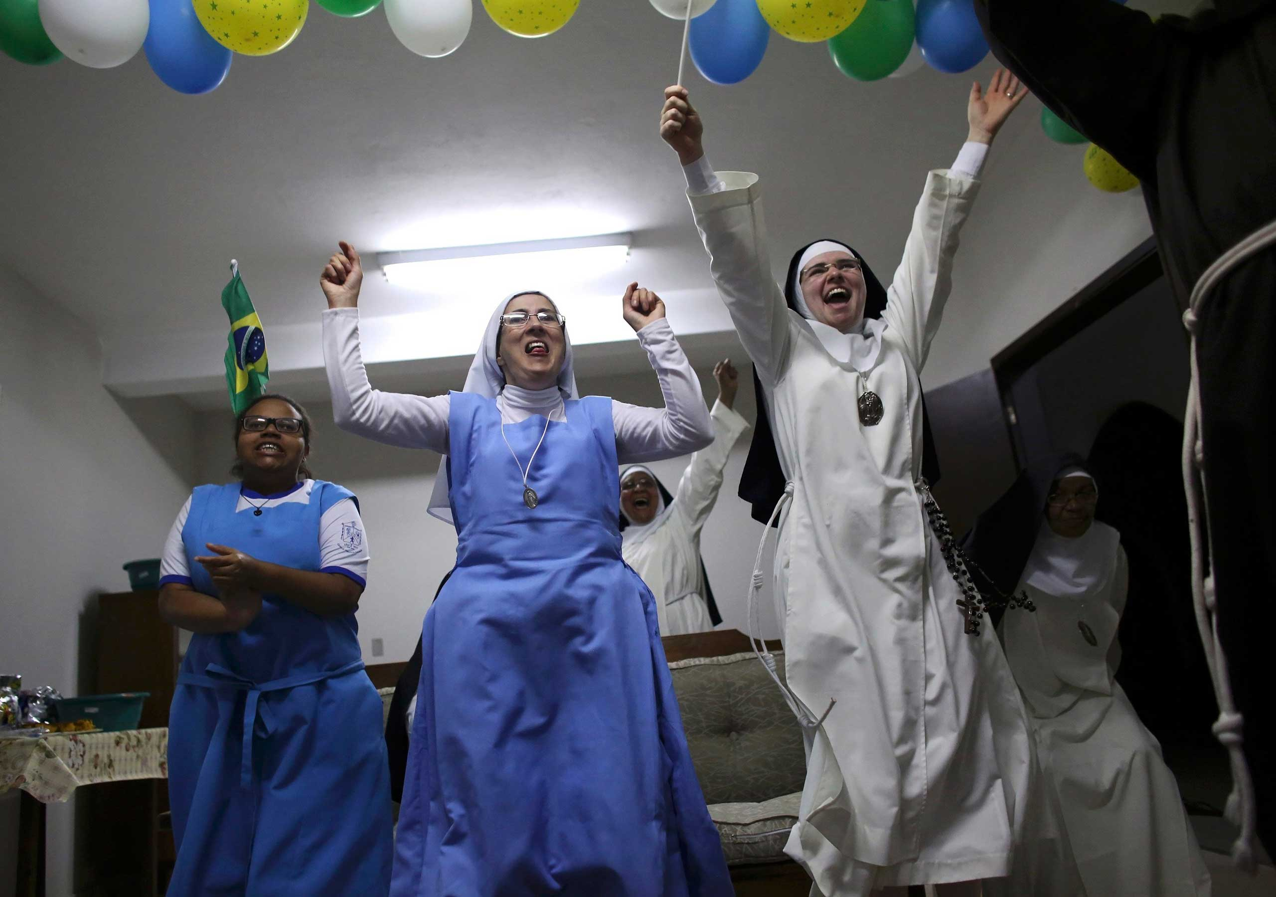 Nuns from the enclosed monastery of Imaculada Conceicao celebrate Brazil's victory as they watch on television at the end of the 2014 World Cup quarter-final soccer match between Brazil and Colombia, in Piratininga, Sao Paulo state, Brazil, July 4, 2014.