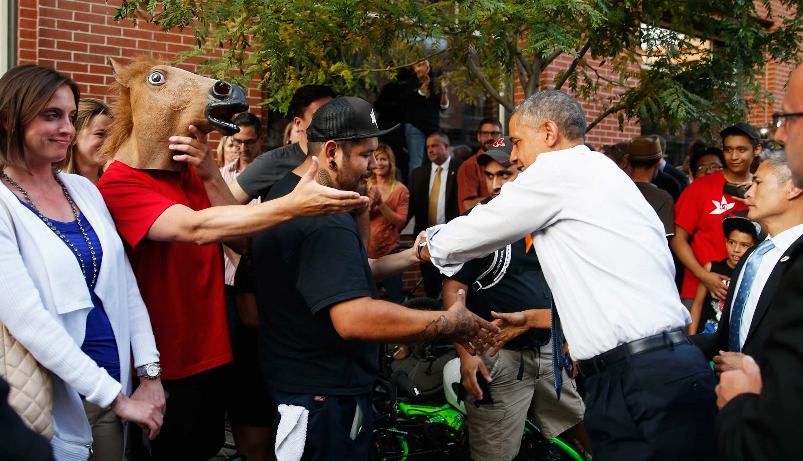 A man wearing a horse mask reaches out to shake hands with U.S. President Barack Obama during a walkabout in Denver, July 8, 2014.