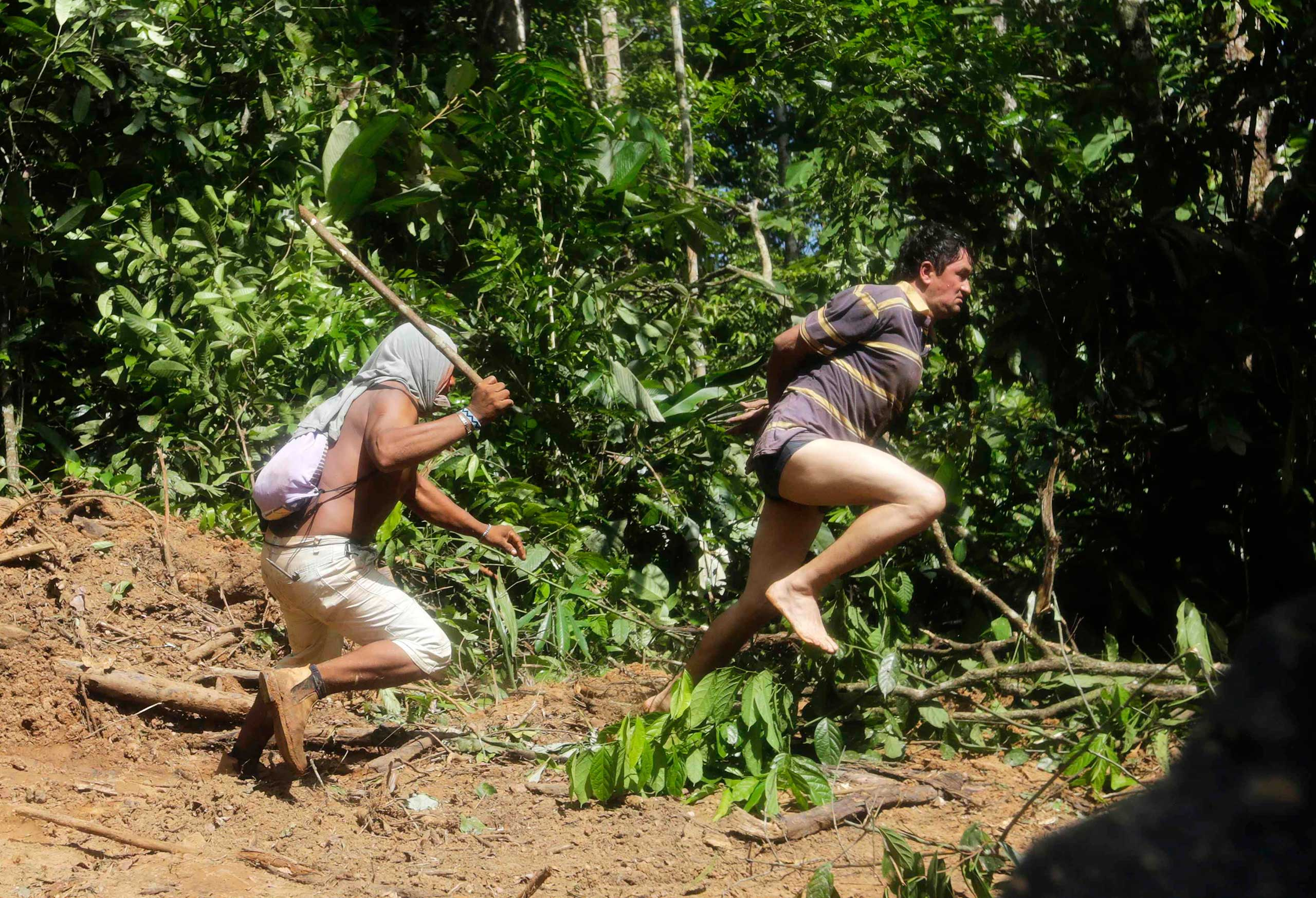 A Ka'apor warrior chases a logger who tried to escape after he was captured during a jungle expedition to search for and expel loggers from the Alto Turiacu Indian territory, northeast of Maranhao state, Amazon basin, August 7, 2014.