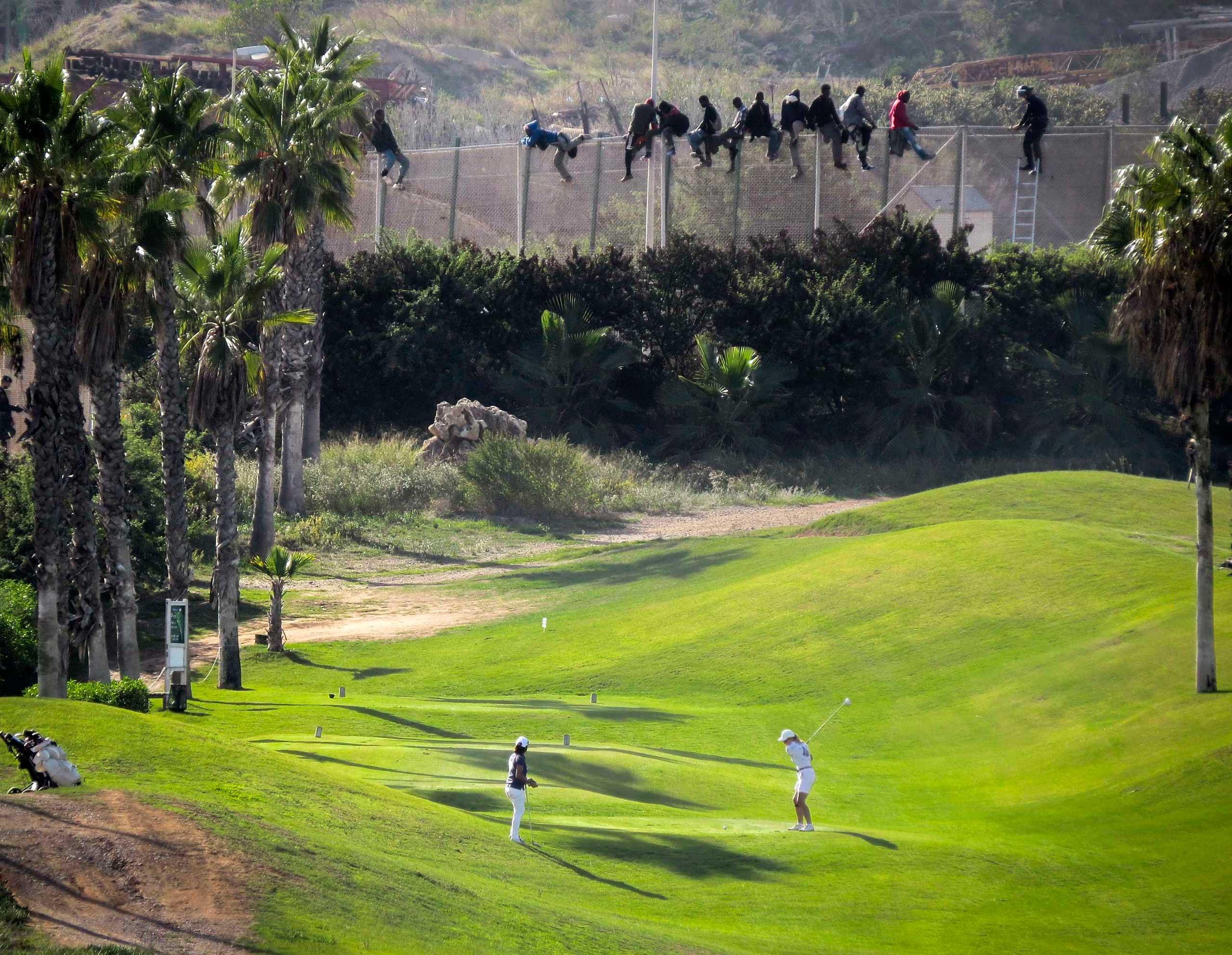 A golfer plays as African migrants sit atop a border fence during an attempt to cross into the  Spanish north African enclave of Melilla, Oct. 22, 2014.