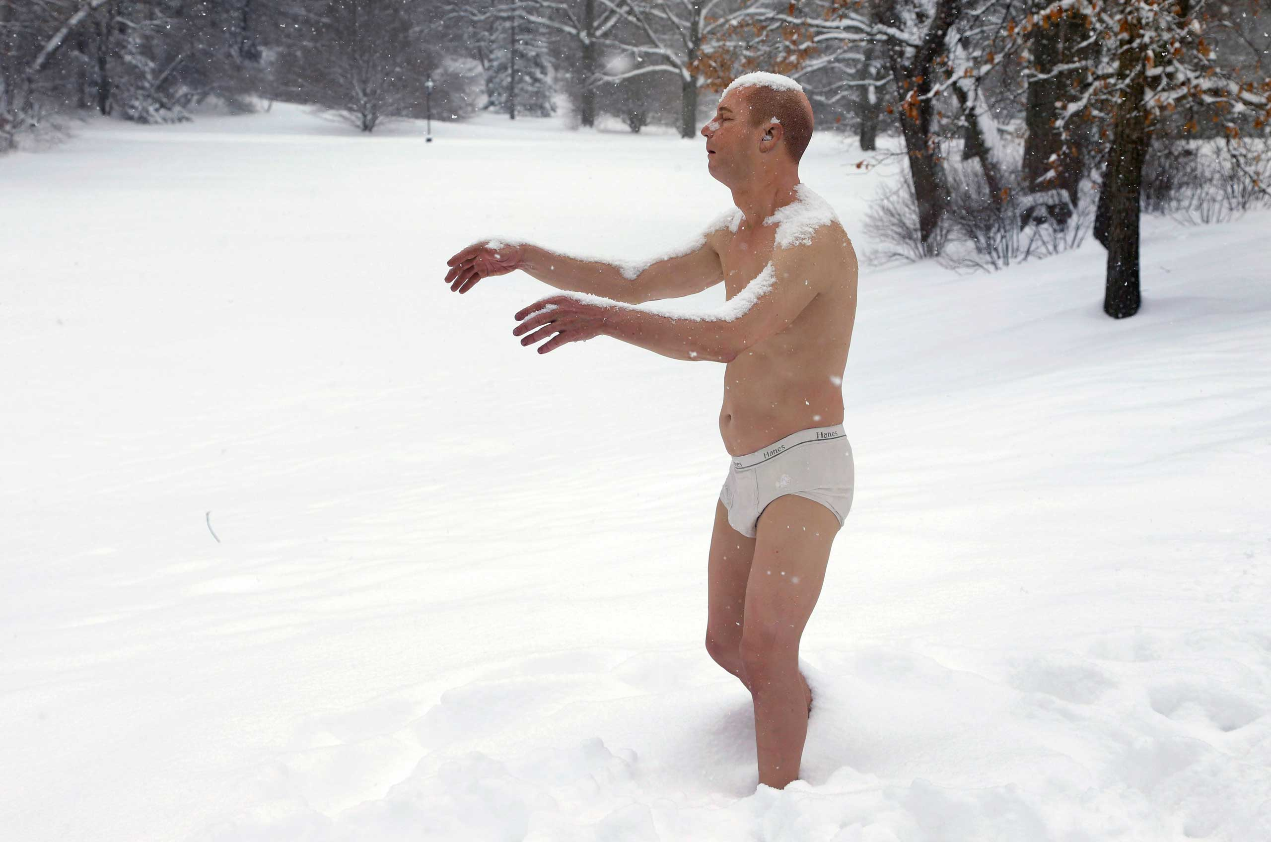 A statue of a man sleepwalking in his underpants is surrounded by snow on the campus of Wellesley College, in Wellesley, Mass., Feb. 5, 2014.