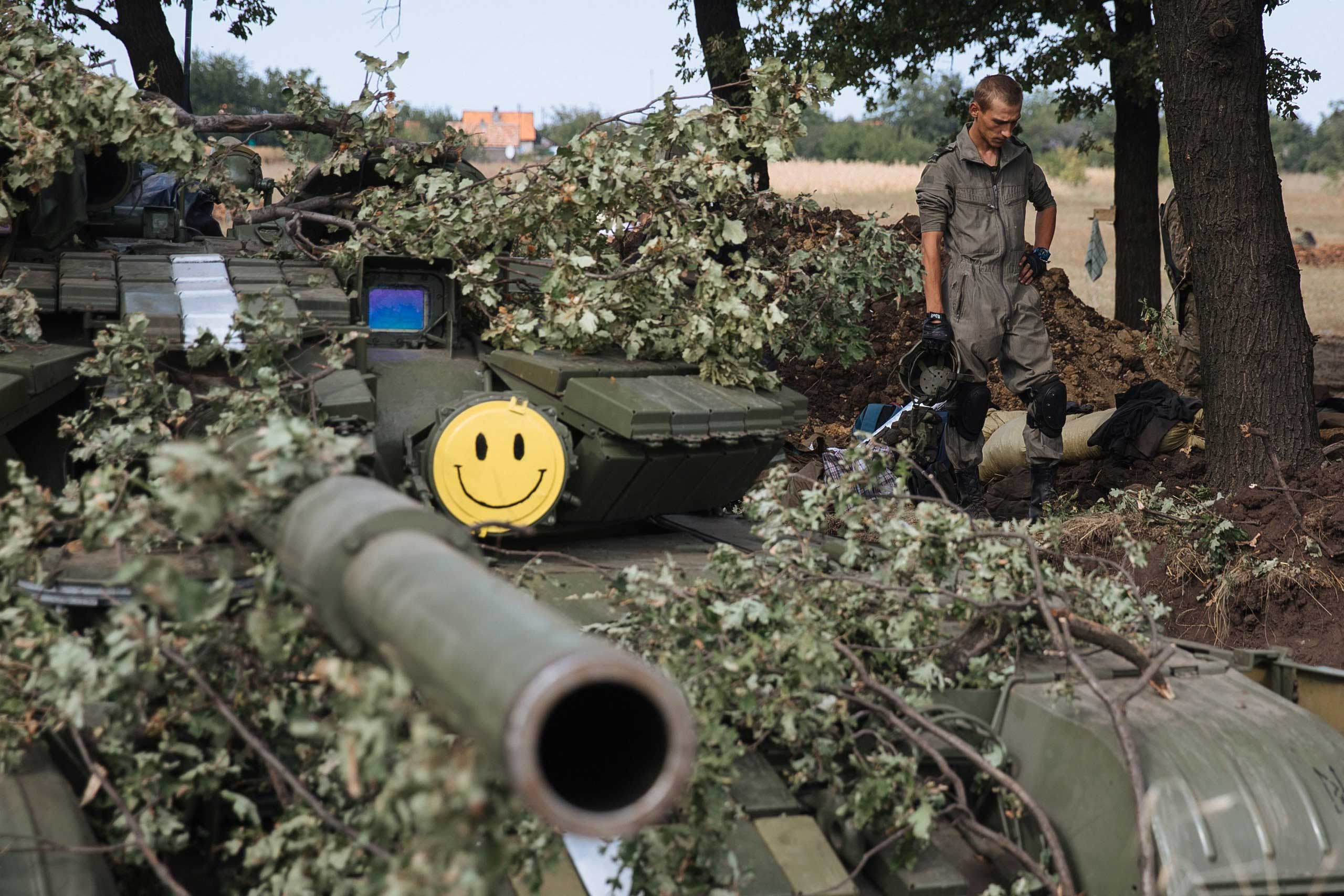 Ukrainian fighters partly wearing non-official uniforms stands next to a tank in a military camp on the front line near Pervomaysk city of Lugansk region, Ukraine, Sept. 12, 2014.
