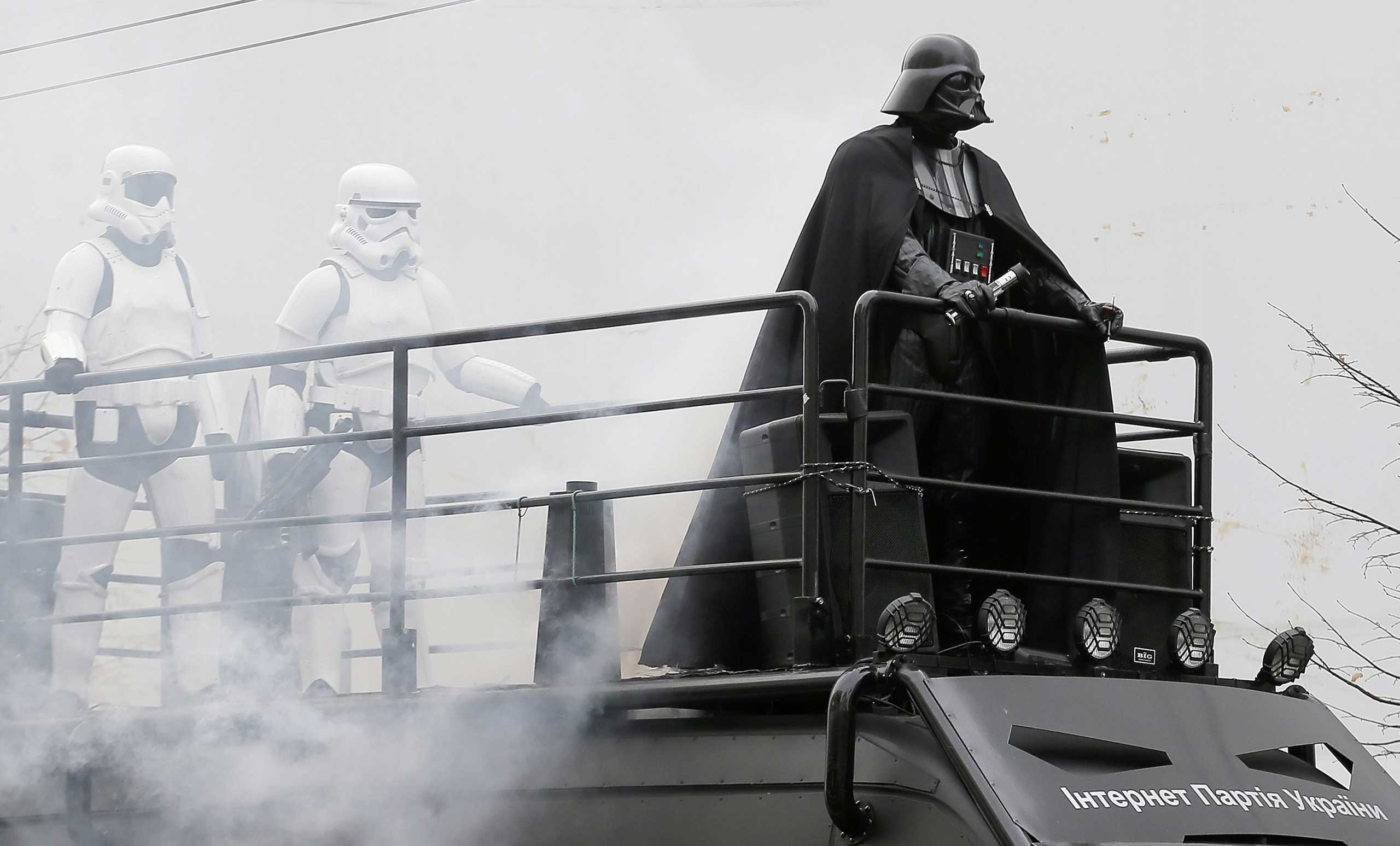 An impersonator of Star Wars character 'Darth Vader' stands on the roof of a van during an election campaign event for the Ukrainian Internet Party. Party members  have legally changed their names to  resemble 'Star Wars'  characters. Kiev,  Oct. 21, 2014.