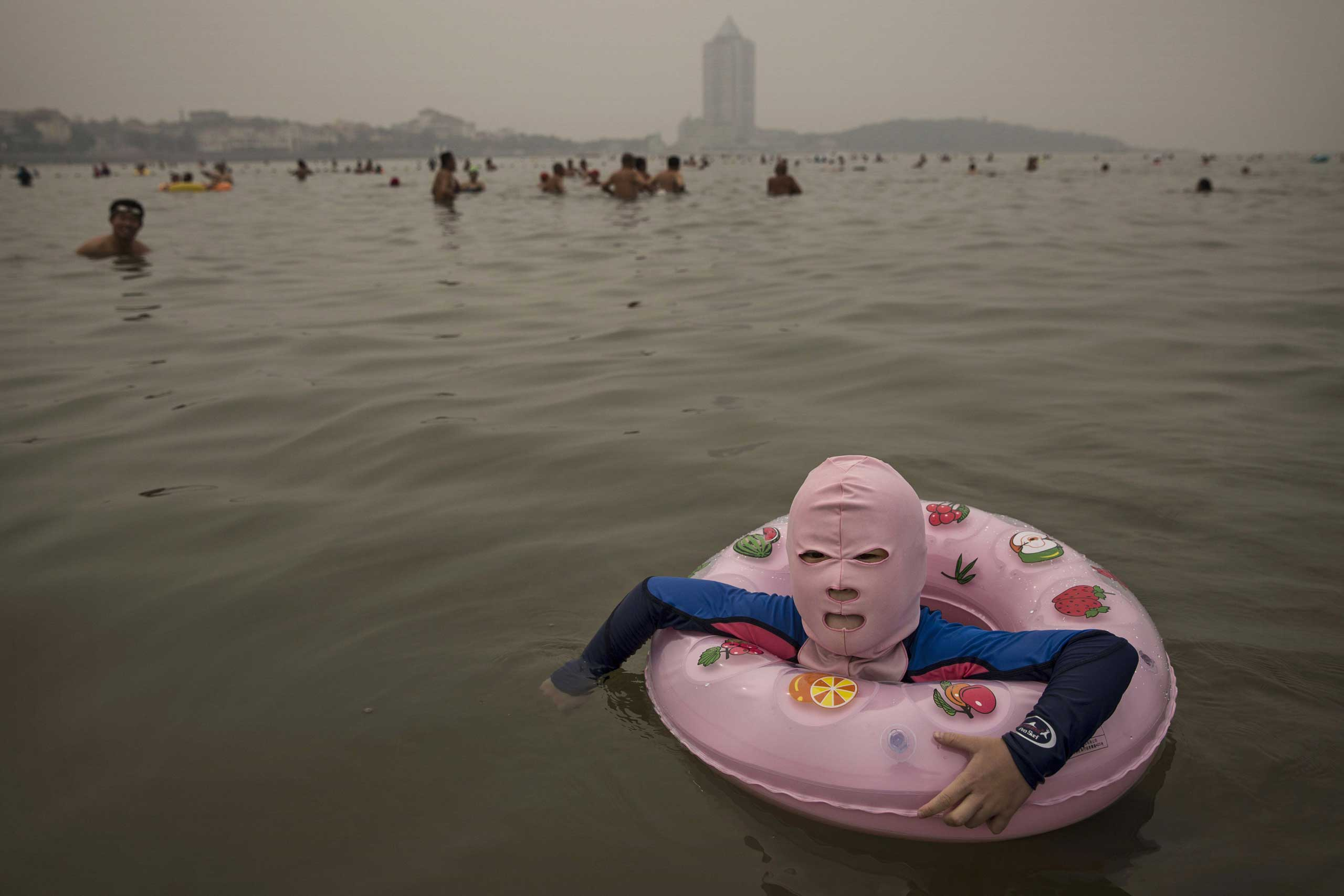 A Chinese girl wears a face-kini to protect her from jellyfish stings, algae and the sun's ultraviolet rays as she floats in the water on the Yellow Sea in Qingdao, China, Aug. 21, 2014.