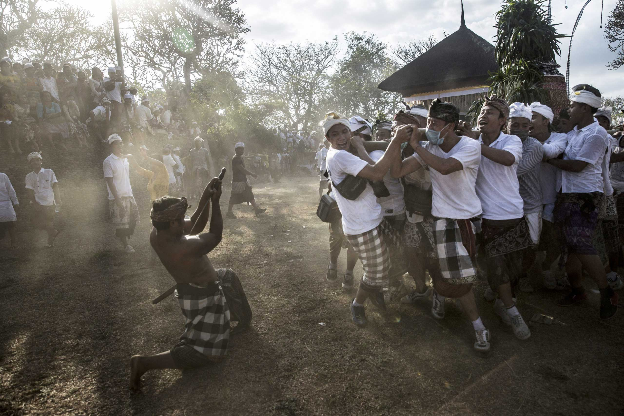 A Balinese man in a state of trance stabs his chest in front of a palanquin, the symbol of god, during Ngusaba Gumang Ritual in Karangasem, Bali, Indonesia, Oct. 6, 2014.