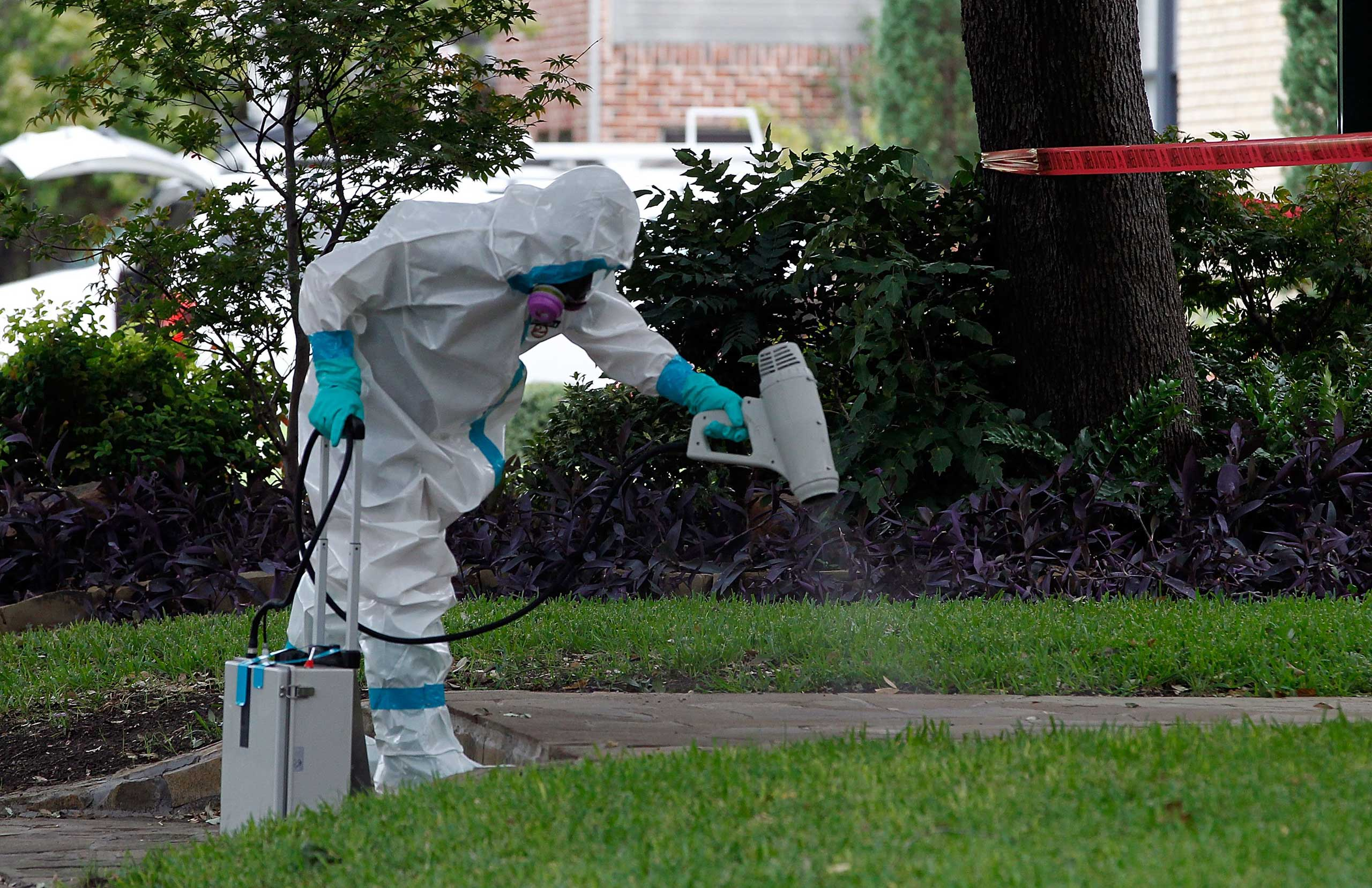 A man dressed in protective hazmat clothing treats the sidewalk in front of an apartment where a second person diagnosed with the Ebola virus lives, Dallas, Oct. 12, 2014.