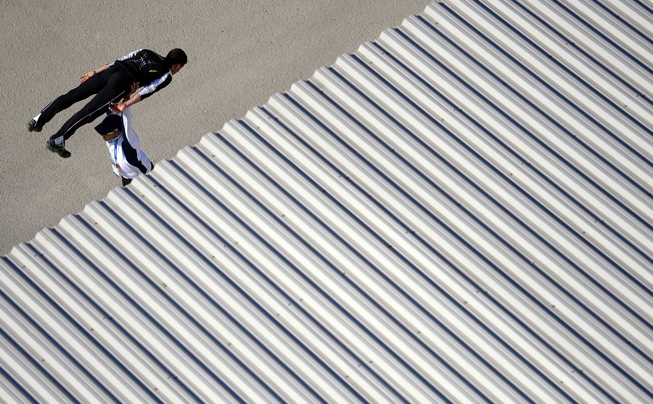 An athlete warms up with his coach prior to the Men's individual Gundersen large hill/10 km Nordic combined training at the Sochi 2014 Winter Olympics at the RusSki Gorki Ski Jumping Center in Sochi, Russia. Feb. 15, 2014.
