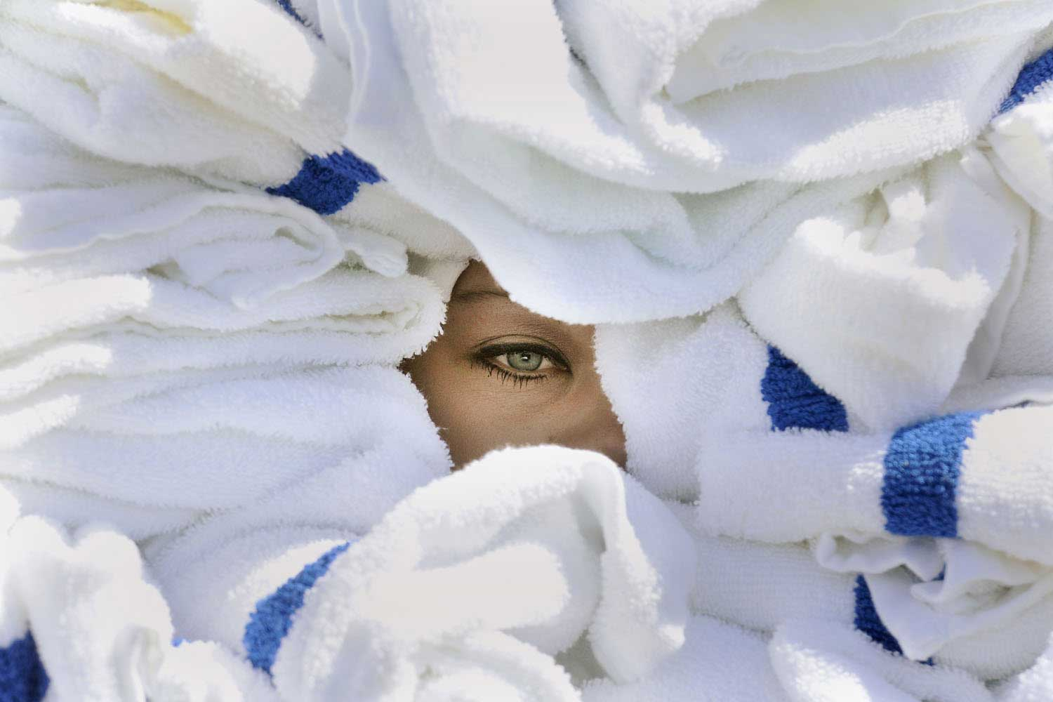 Rebecca Redwine from Grandma's in the Park has one eye visible from between nearly 100 towels, as she competes in the towel carrying contest during the 10th annual Iron Range Housekeeping Olympics held in AmericInn Lodge in Virginia, Minn., Sept. 8, 2014.