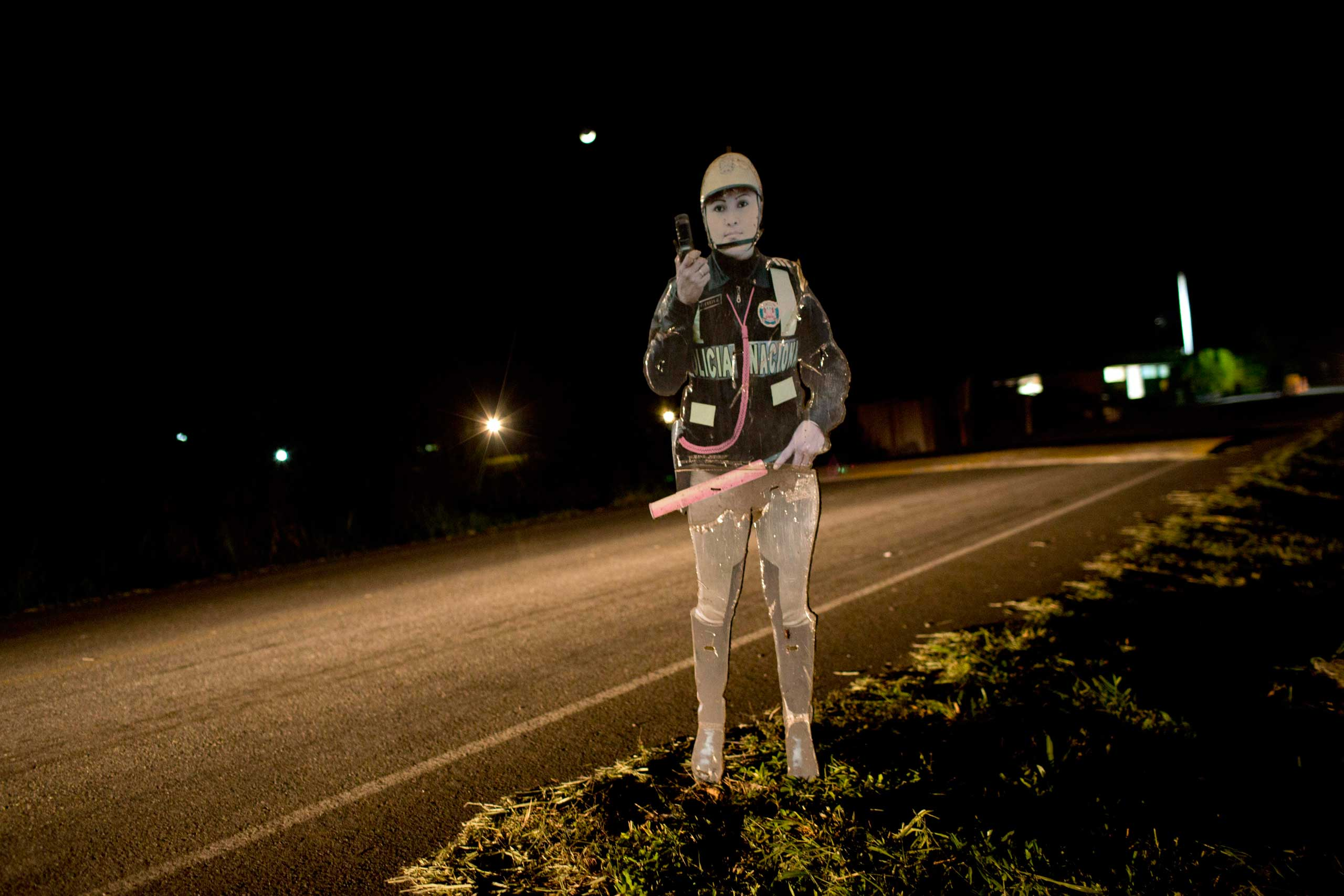 A cutout of a policewoman is seen on the highway that connects the Peruvian towns of Aucayacu and Tocache. The cutout is meant to remind potential criminals that police are in the area, Peru, Sept. 26, 2014.