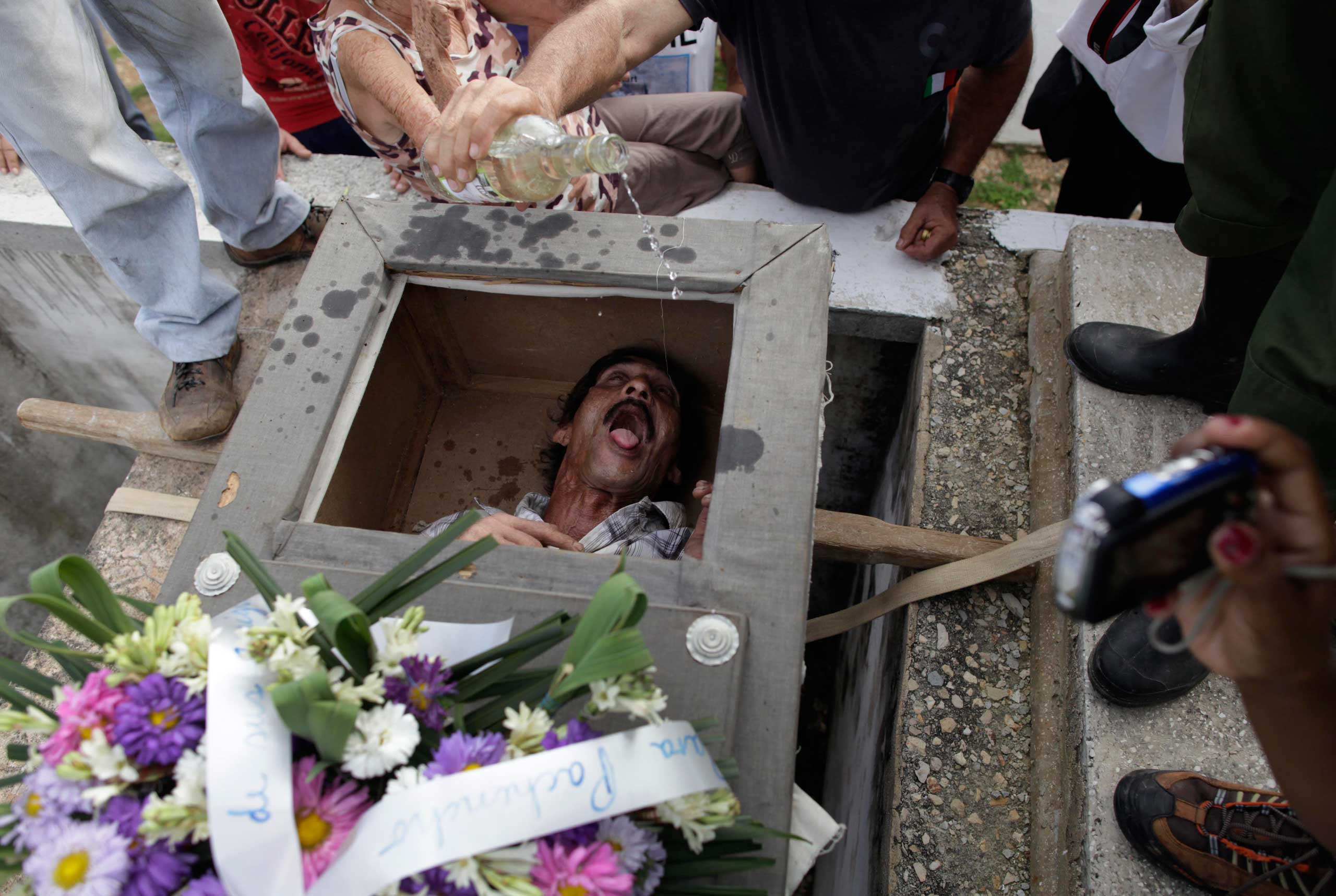 Divaldo Aguiar, who is playing the part of character Pachencho, lies inside a mock coffin as villagers splash rum into his mouth during the annual  Burial of Pachencho  celebration at a cemetery in Santiago de Las Vegas, Cuba, Feb. 5, 2014.