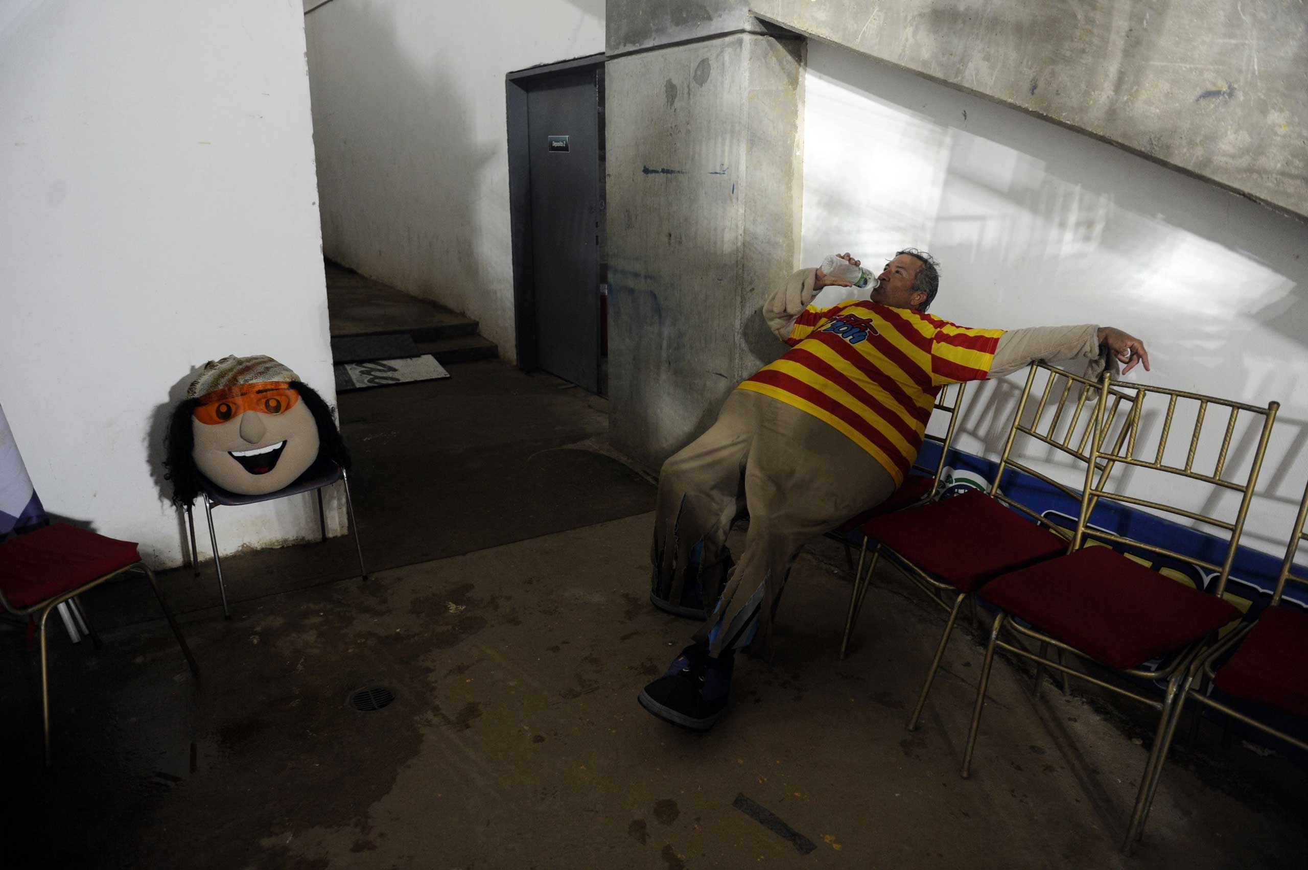 The man that works as the mascot  Margarito  for the 2014 Caribbean baseball series rests at the backstage during a game between Dominican Republic's Tigres de Licey and Venezuela's Navegantes del Magallanes in Porlamar city, Margarita Island, Nueva Esparta state, Venezuela, Feb. 4, 2014.
