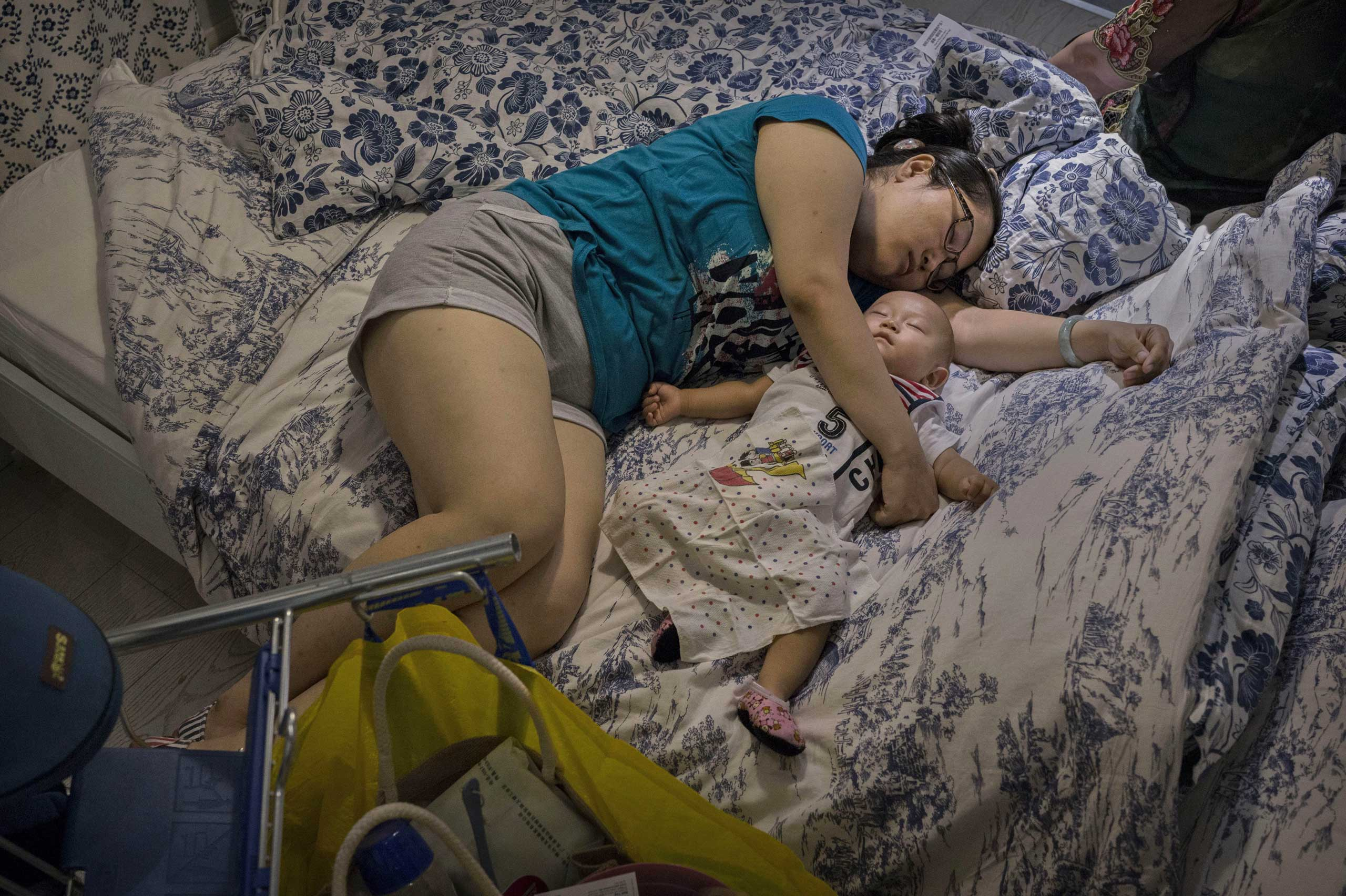 A Chinese shopper sleeps with her child on a bed in the showroom of an IKEA store in Beijing, July 6, 2014.