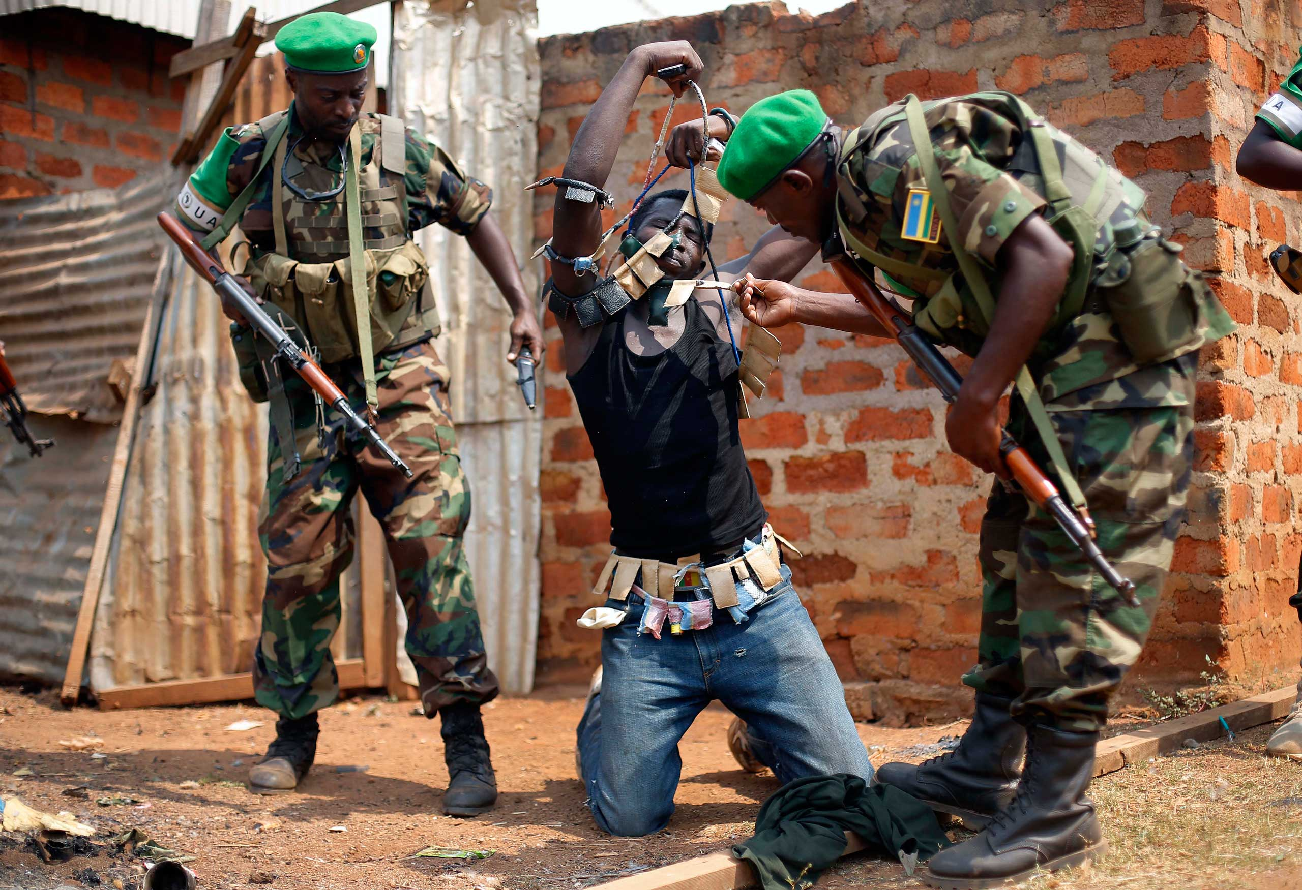 Rwandan African Union peacekeepers remove the lucky charms from a suspected Anti-balaka Christian man who was found with a rifle and a grenade following looting in the Muslim market of the PK13 district of Bangui, Central African Republic, Jan. 22, 2014.