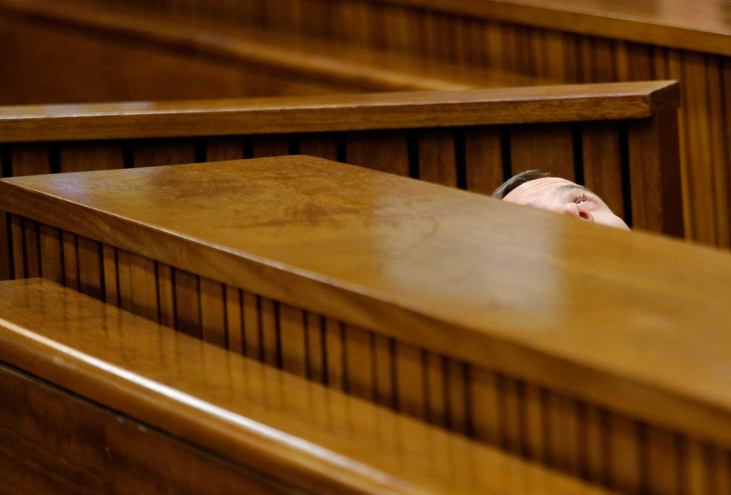 South African Paralympic athlete Oscar Pistorius is seen leaning back after applying eye drops as he prepares himself for another day in the dock during his murder trial in Pretoria, South Africa, March 14, 2014.