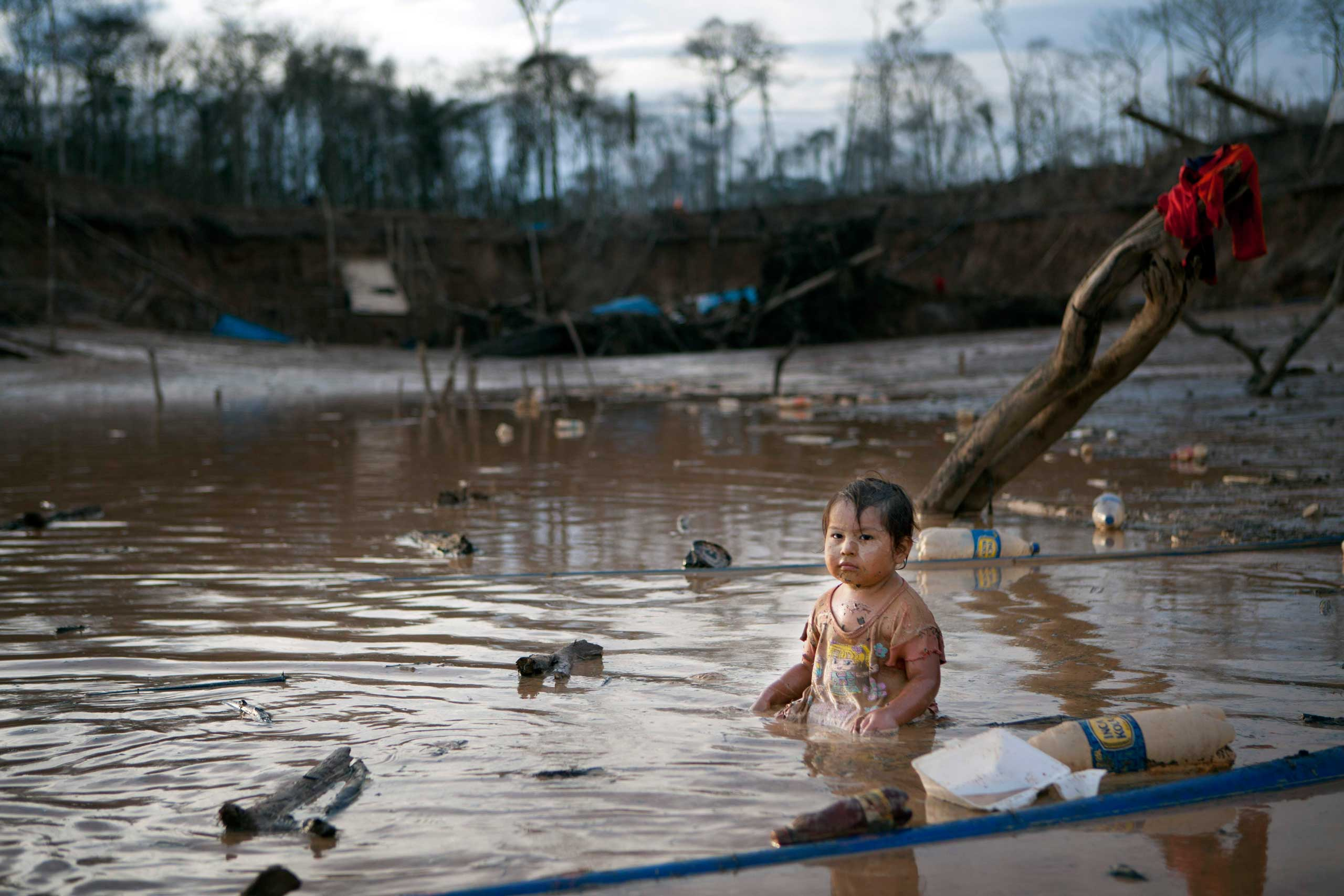 Prisaida, 2, sits in the shallow waters of a polluted lagoon as her parents mine for gold nearby in La Pampa in Peru's Madre de Dios region, May 3, 2014.