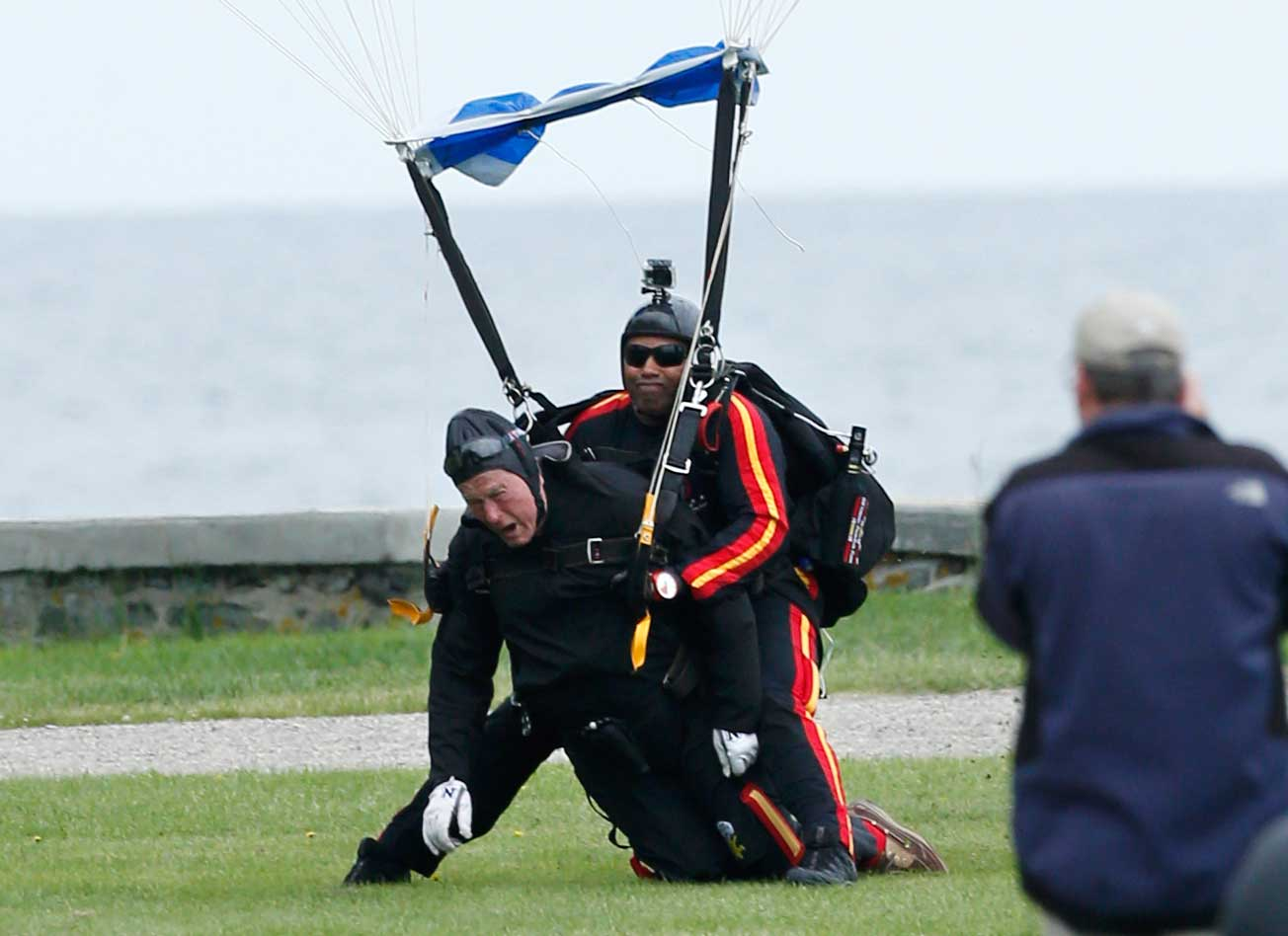 Former President George H.W. Bush, left, strapped to Sgt. 1st Class Mike Elliott, a retired member of the Army's Golden Knights parachute team, land on the lawn at St. Anne's Episcopal Church after making a tandem parachute jump near Bush's summer home in Kennebunkport, Maine, Thursday, June 12, 2014.
