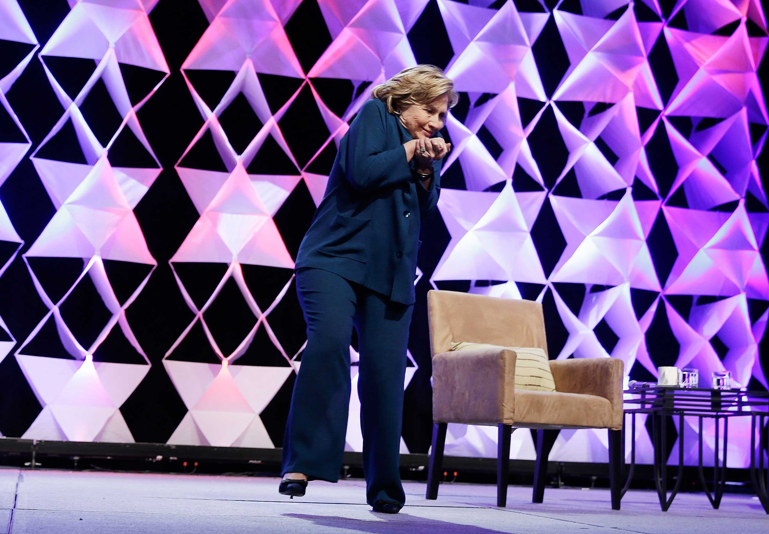 Former Secretary of State Hillary Clinton ducks after a woman threw an object toward her while she was delivering remarks at the Institute of Scrap Recycling Industries conference in in Las Vegas, Nev., April 10, 2014.
