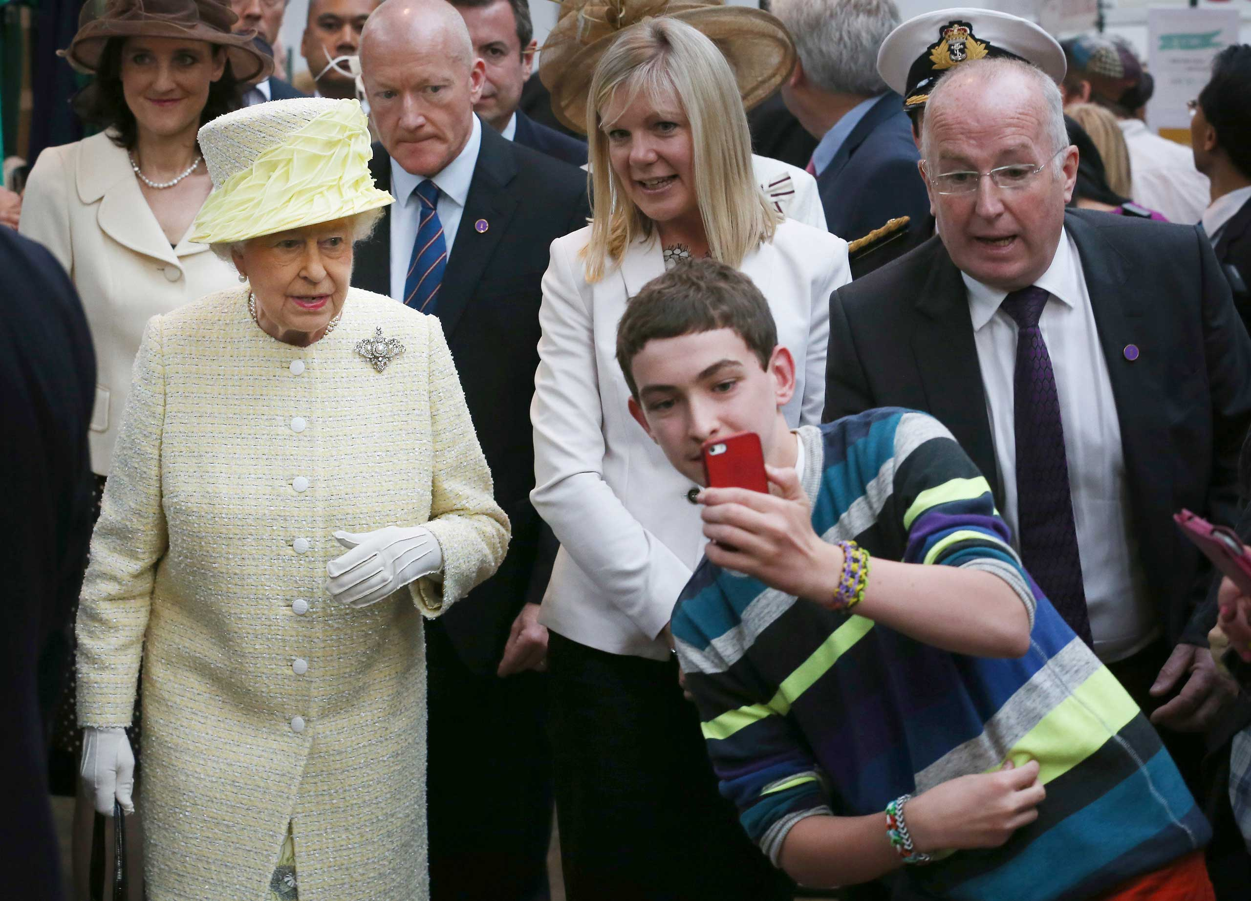 A local youth takes a selfie in front of Queen Elizabeth II during her visit to St George's indoor market in Belfast, Northern Ireland, June 24, 2014.